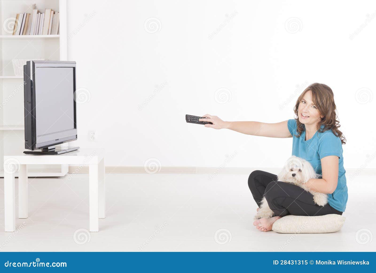 Γυναίκα και σκυλί που προσέχουν τη TV από κοινού