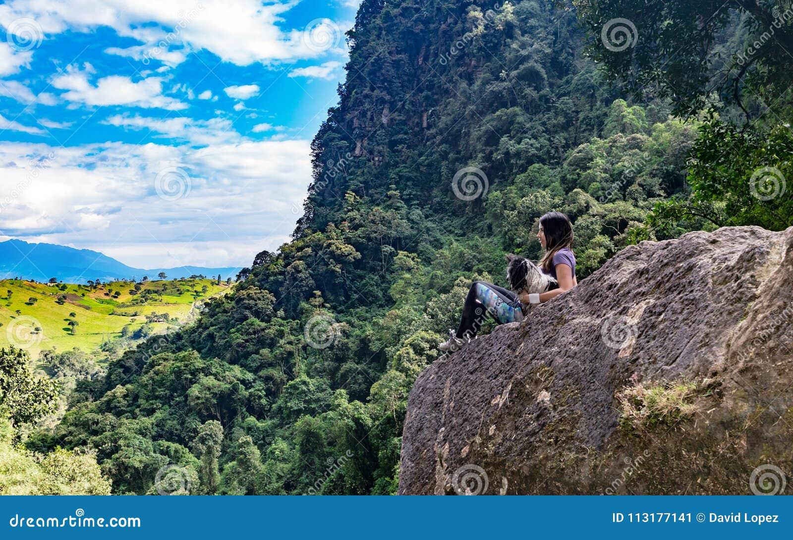 Γυναίκα και το σκυλί της που συλλογίζονται τον ορίζοντα σε έναν βράχο, τρίτο pho
