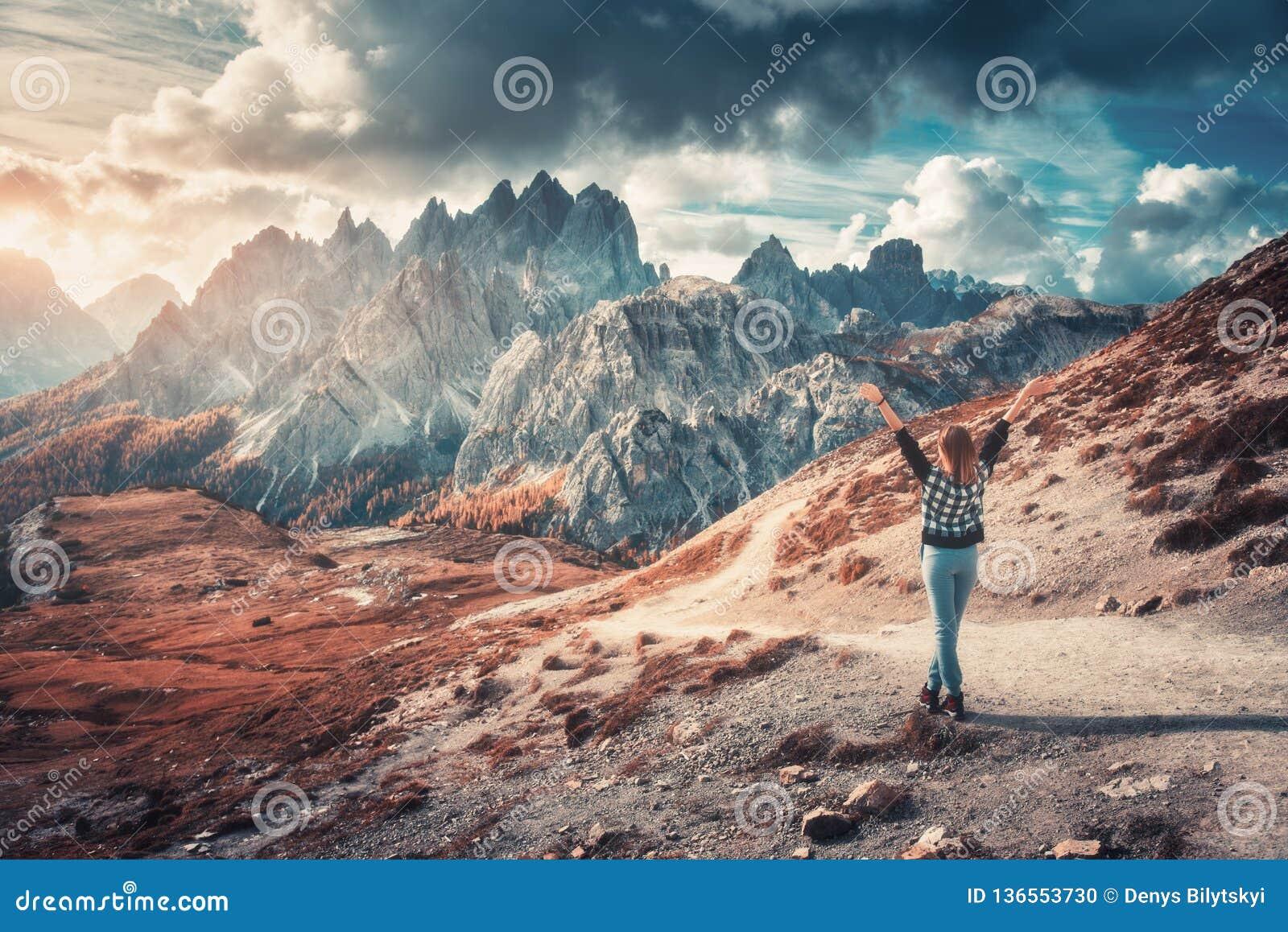 Γυναίκα με αυξημένος επάνω στα όπλα και τα υψηλά βουνά στο ηλιοβασίλεμα