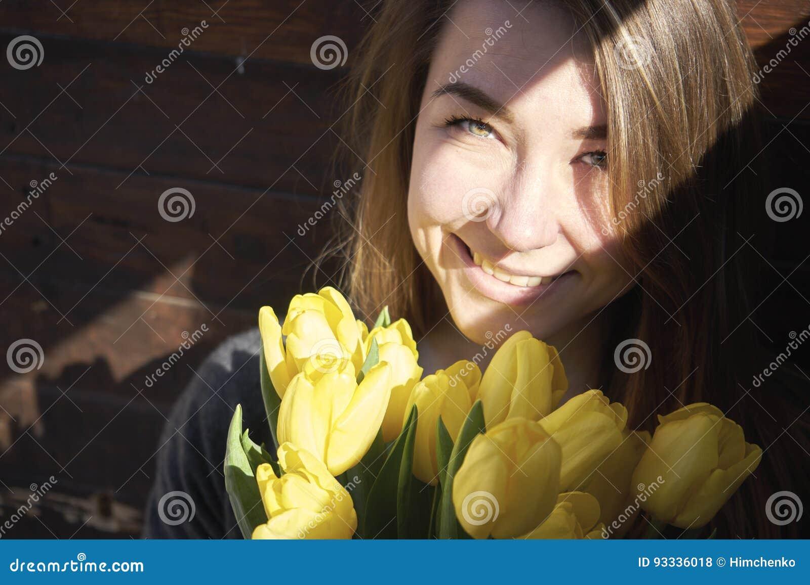 Γυναίκα με τα λουλούδια σε ένα σκοτεινό δωμάτιο