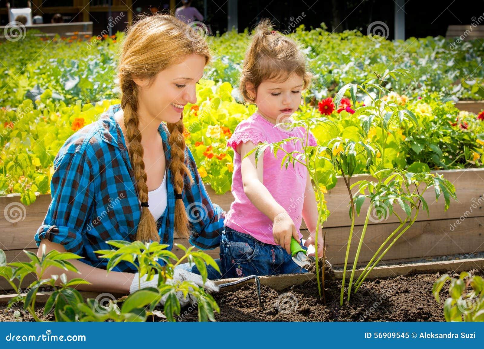Γυναίκα με την λίγη κόρη στον κήπο
