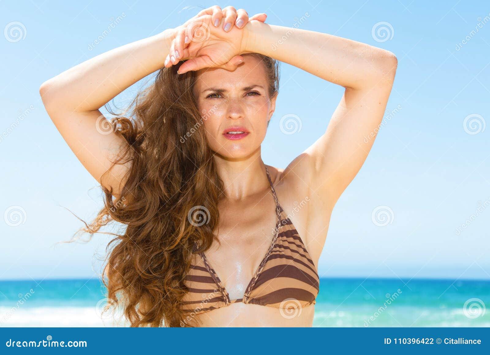 Γυναίκα με τη μακριά τρίχα brunette στην ακτή που εξετάζει την απόσταση