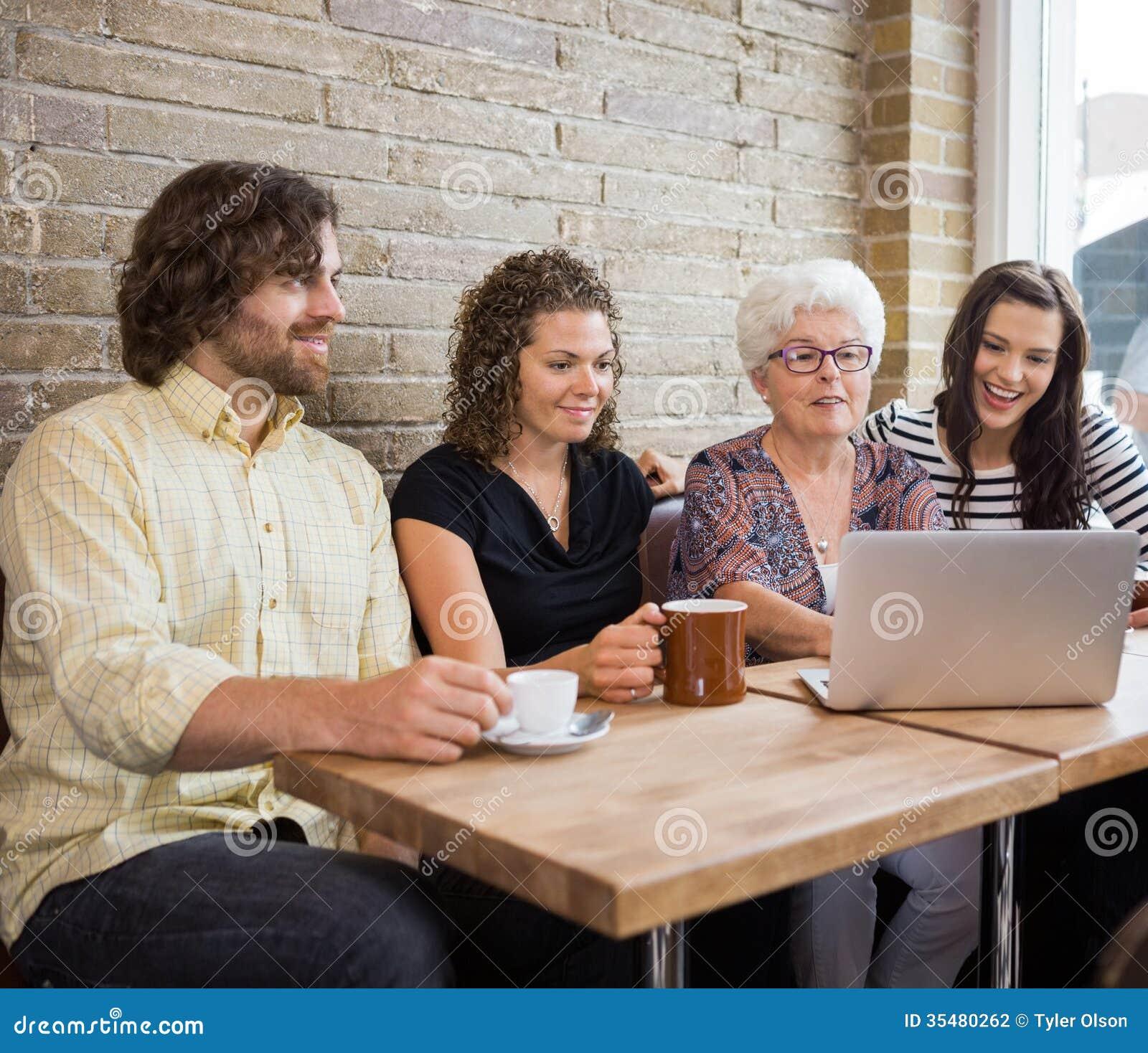 Γυναίκα με τους φίλους που χρησιμοποιούν το lap-top στον πίνακα καφέδων