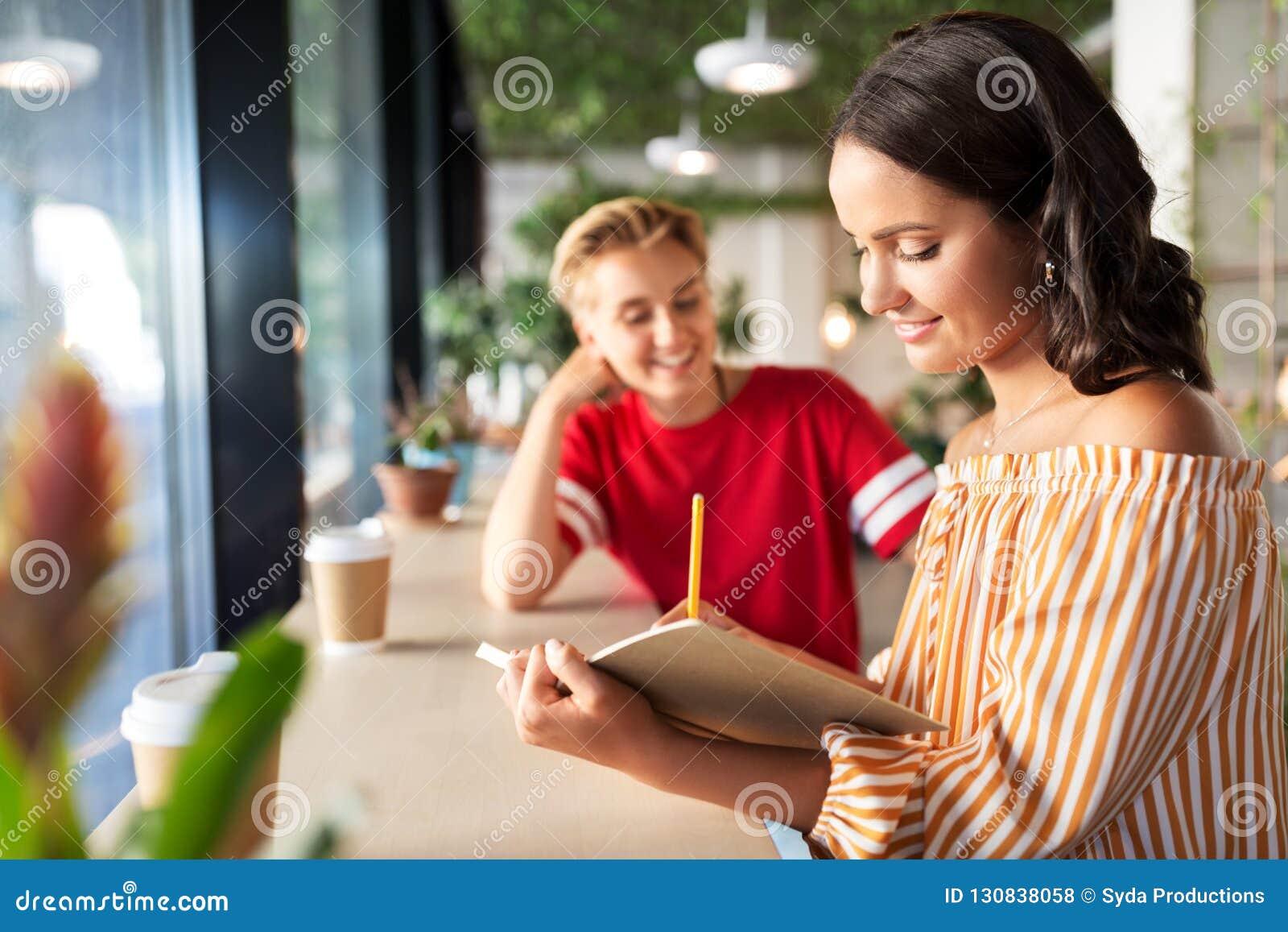Γυναίκα με το φίλο στον καφέ που γράφει στο σημειωματάριο