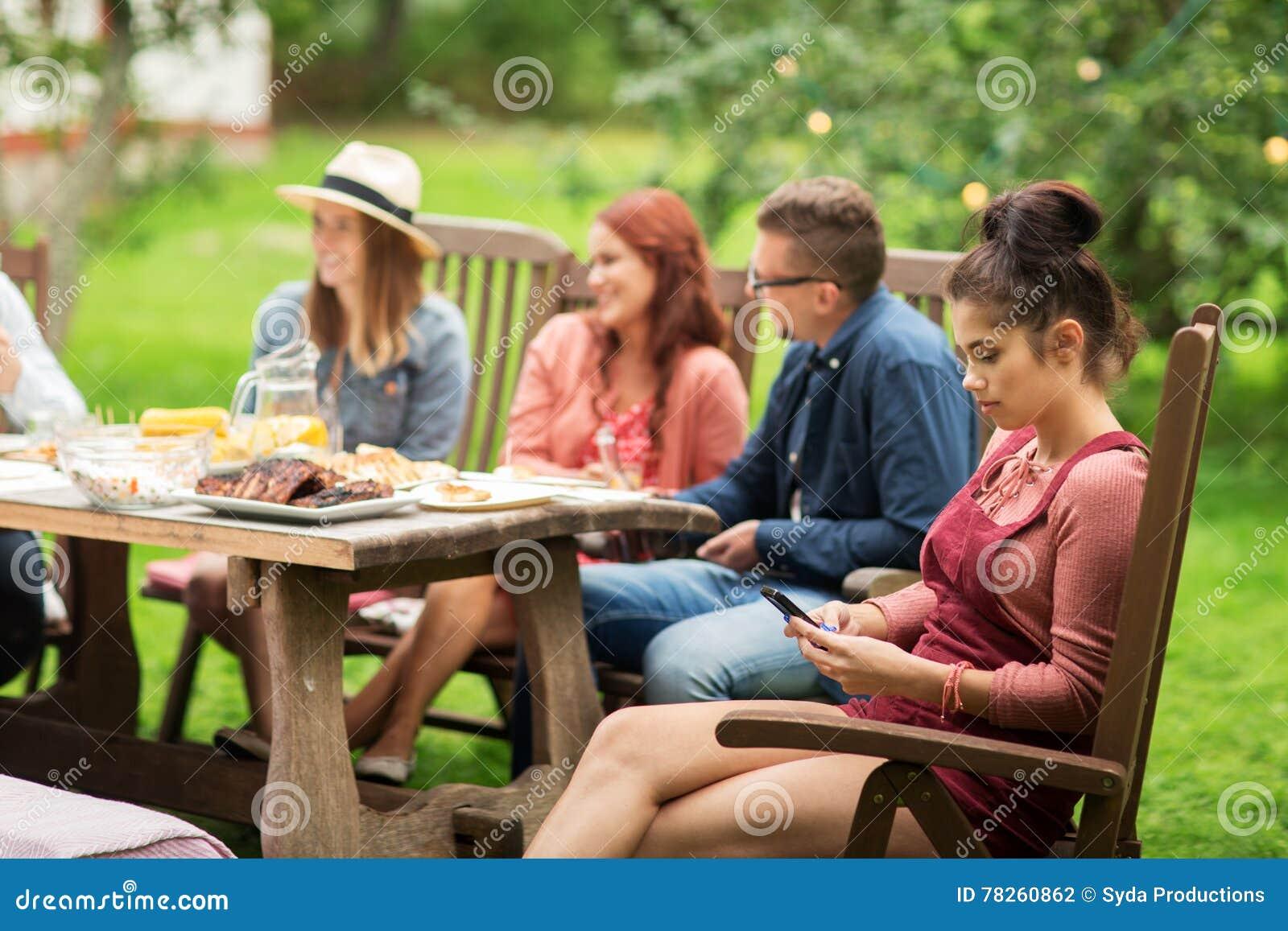 Γυναίκα με το smartphone και φίλοι στο θερινό κόμμα