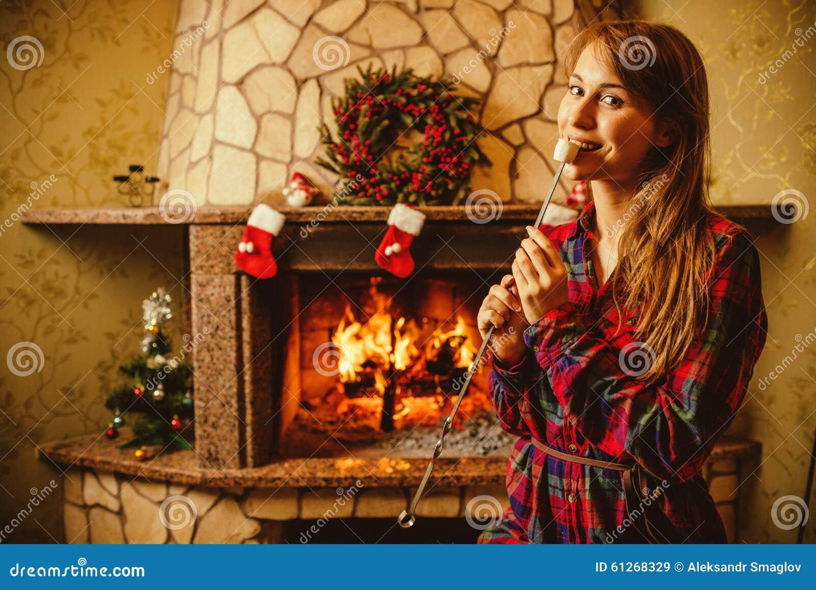 Γυναίκα με marshmallow από την εστία Νέα γυναίκα που χαμογελά και