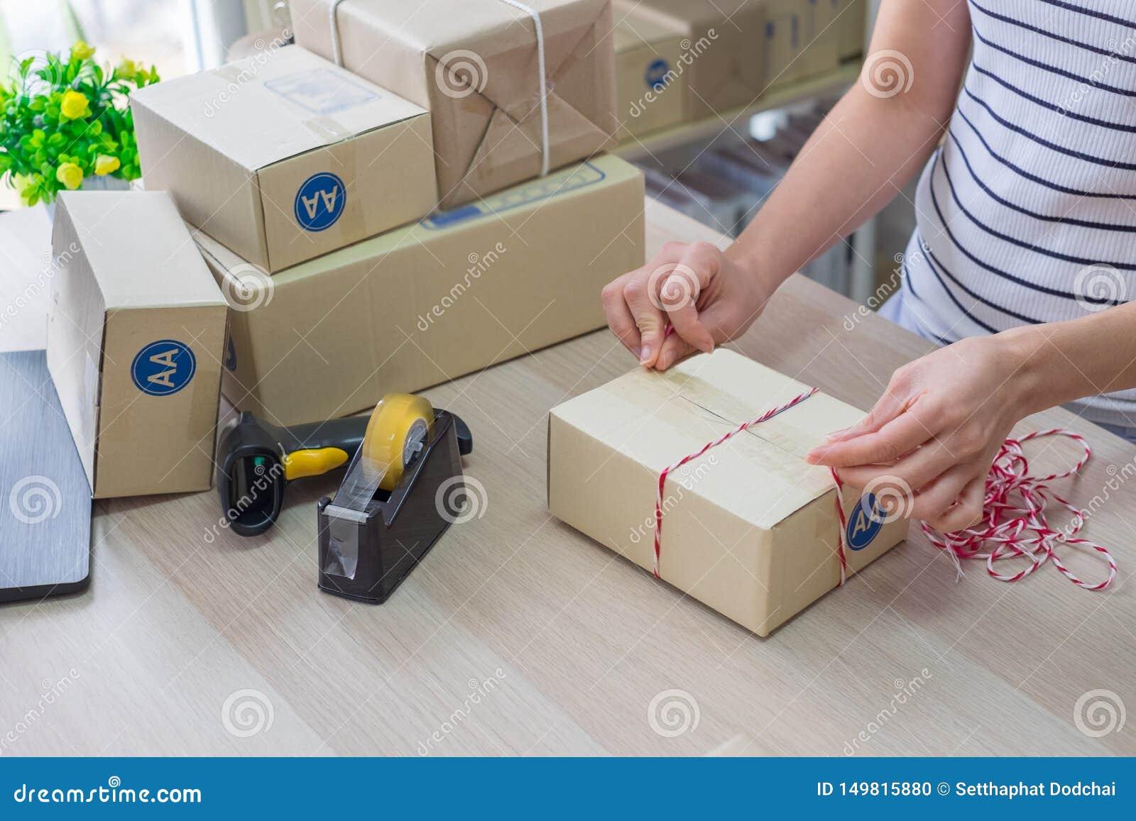 Γυναίκα, μικρή επιχείρηση ξεκινήματος Κουτί από χαρτόνι συσκευασίας ιδιοκτητών στον εργασιακό χώρο Προετοιμάστε το κιβώτιο συσκευ