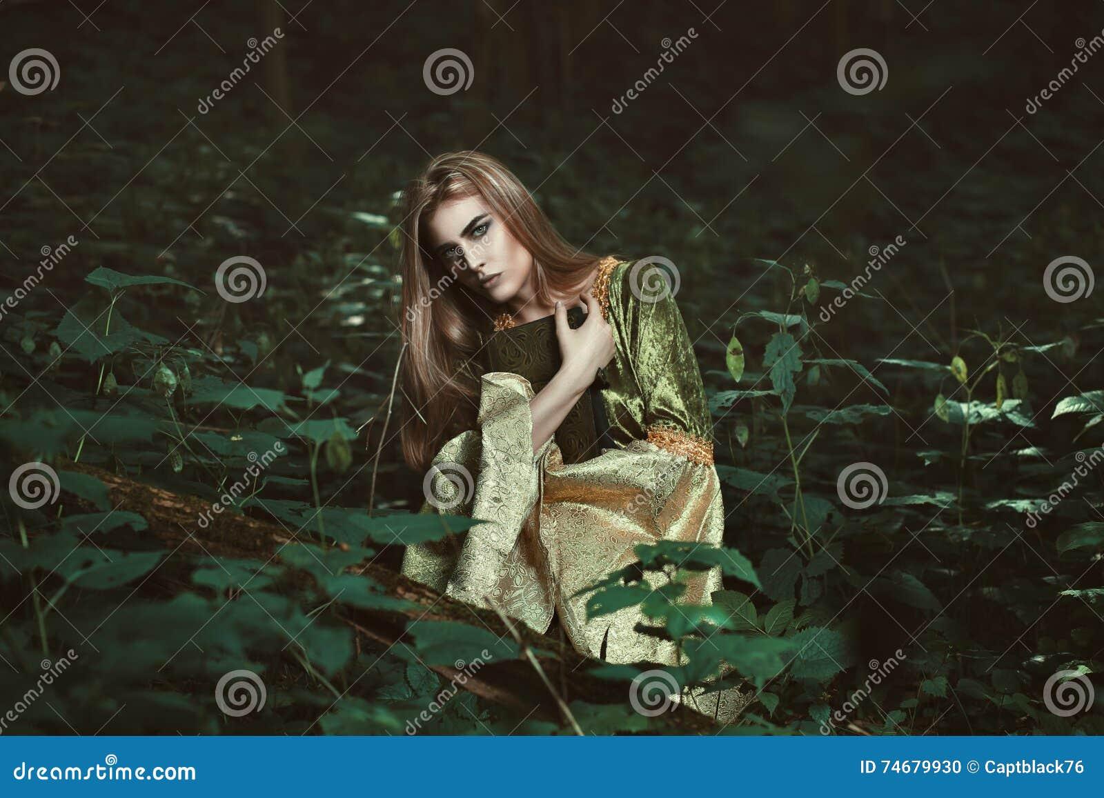 Γυναίκα νεράιδων με ένα βιβλίο στα ξύλα