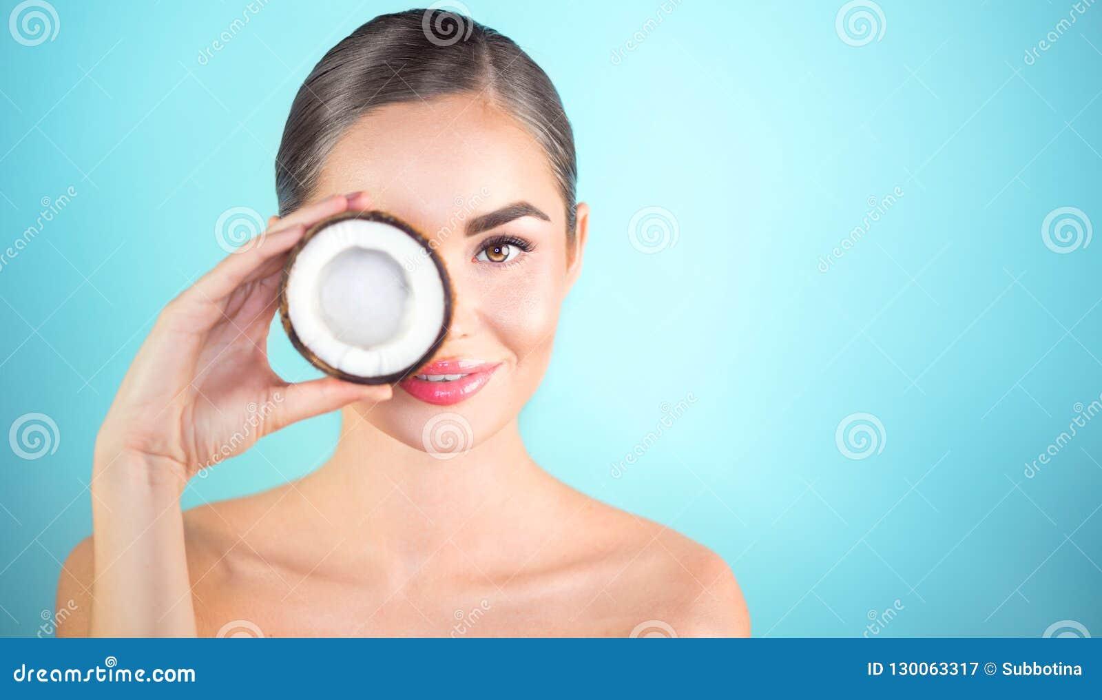 Γυναίκα ομορφιάς με την καρύδα Αρκετά νέο καρύδι και χαμόγελο κοκοφοινίκων εκμετάλλευσης κοριτσιών brunette SPA και skincare
