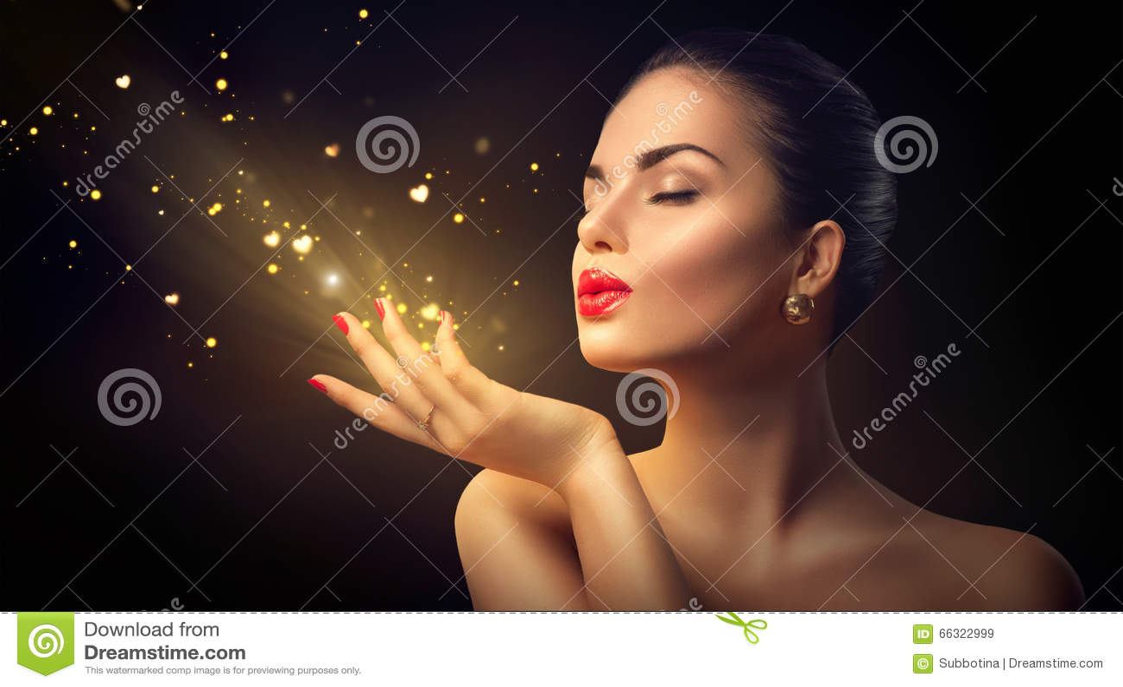 Γυναίκα ομορφιάς που φυσά τη μαγική σκόνη με τις χρυσές καρδιές
