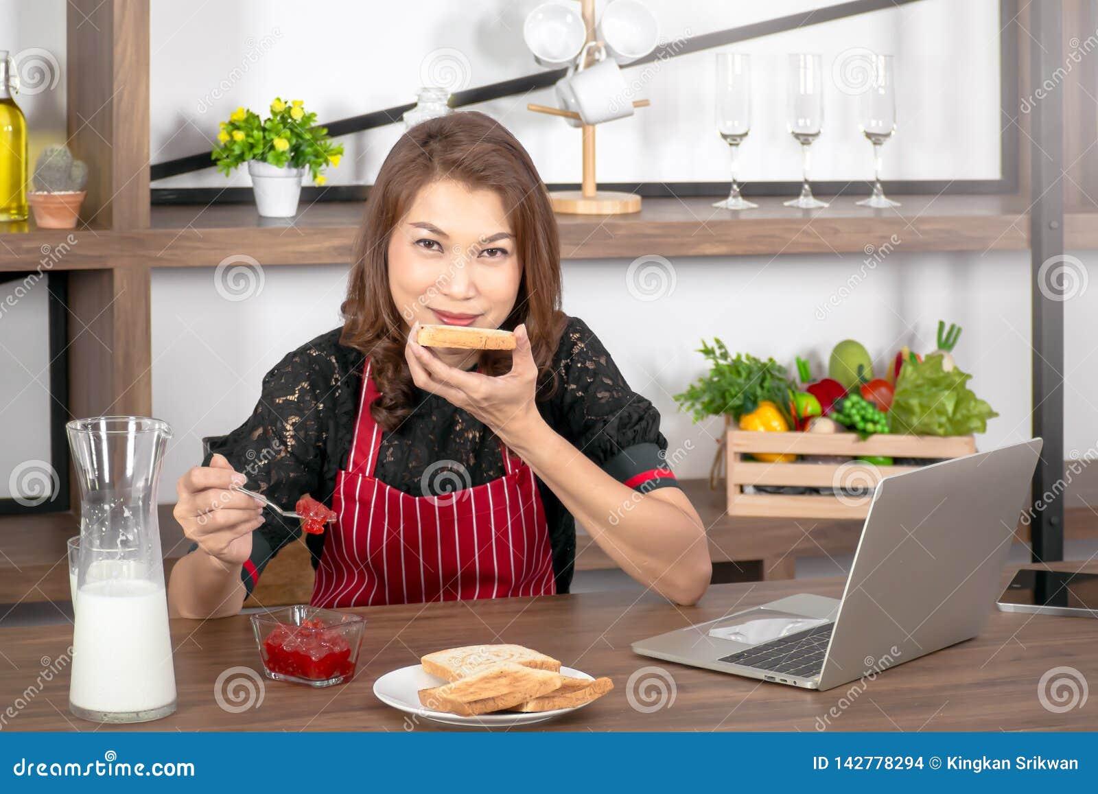 Γυναίκα που έχει τη φρυγανιά με τη μαρμελάδα φραουλών