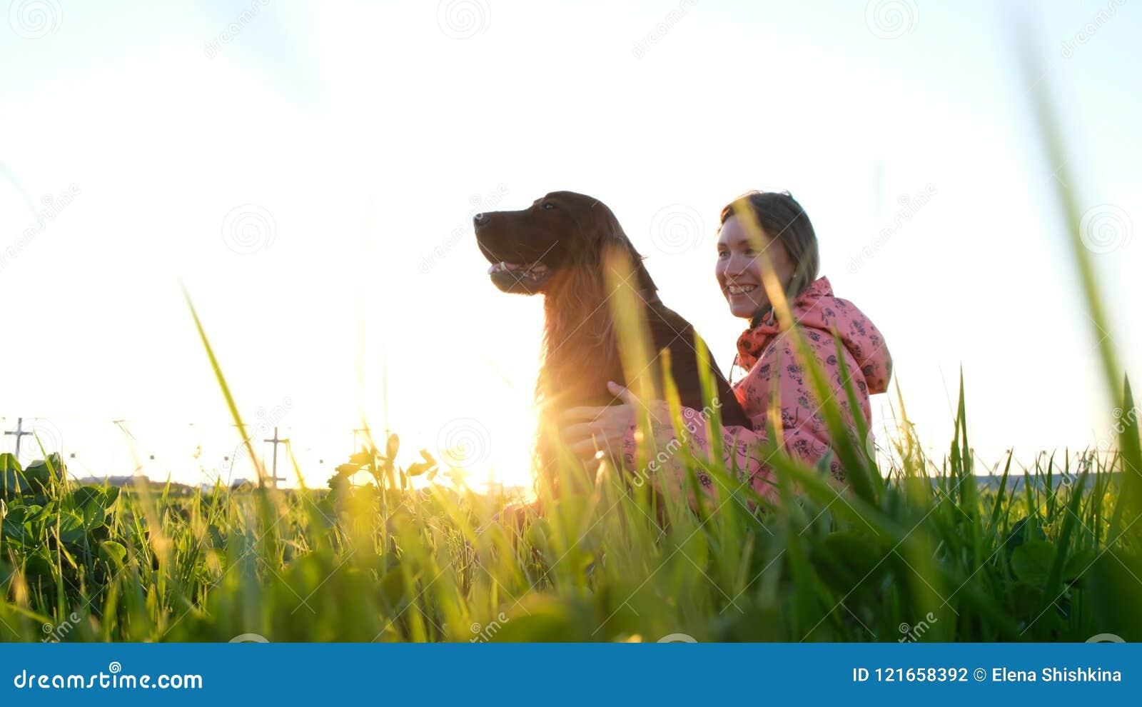 Γυναίκα που αγκαλιάζουν το σκυλί στο ηλιοβασίλεμα και το γέλιο, νέο κορίτσι με τη συνεδρίαση κατοικίδιων ζώων στη χλόη και τη στή