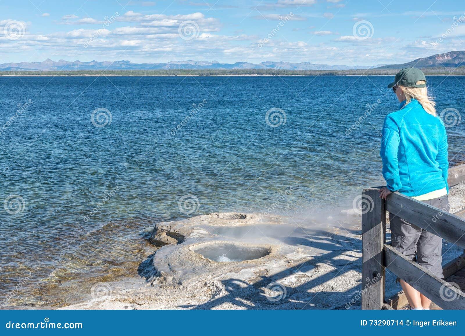 Γυναίκα που αγνοεί geyser στην ακτή της λίμνης Yellowstone