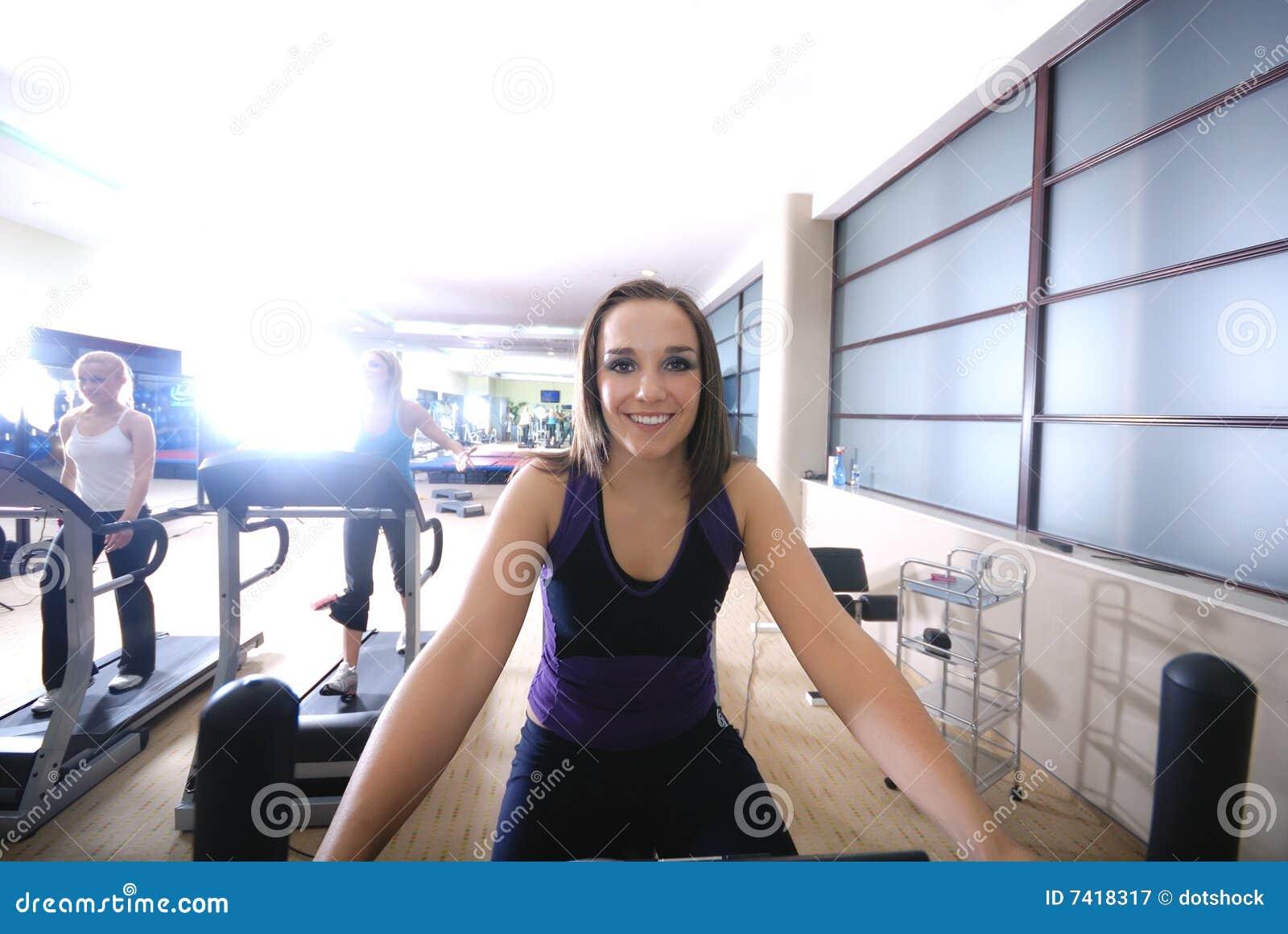 Γυναίκα που επιλύει στην περιστροφή του ποδηλάτου στη γυμναστική