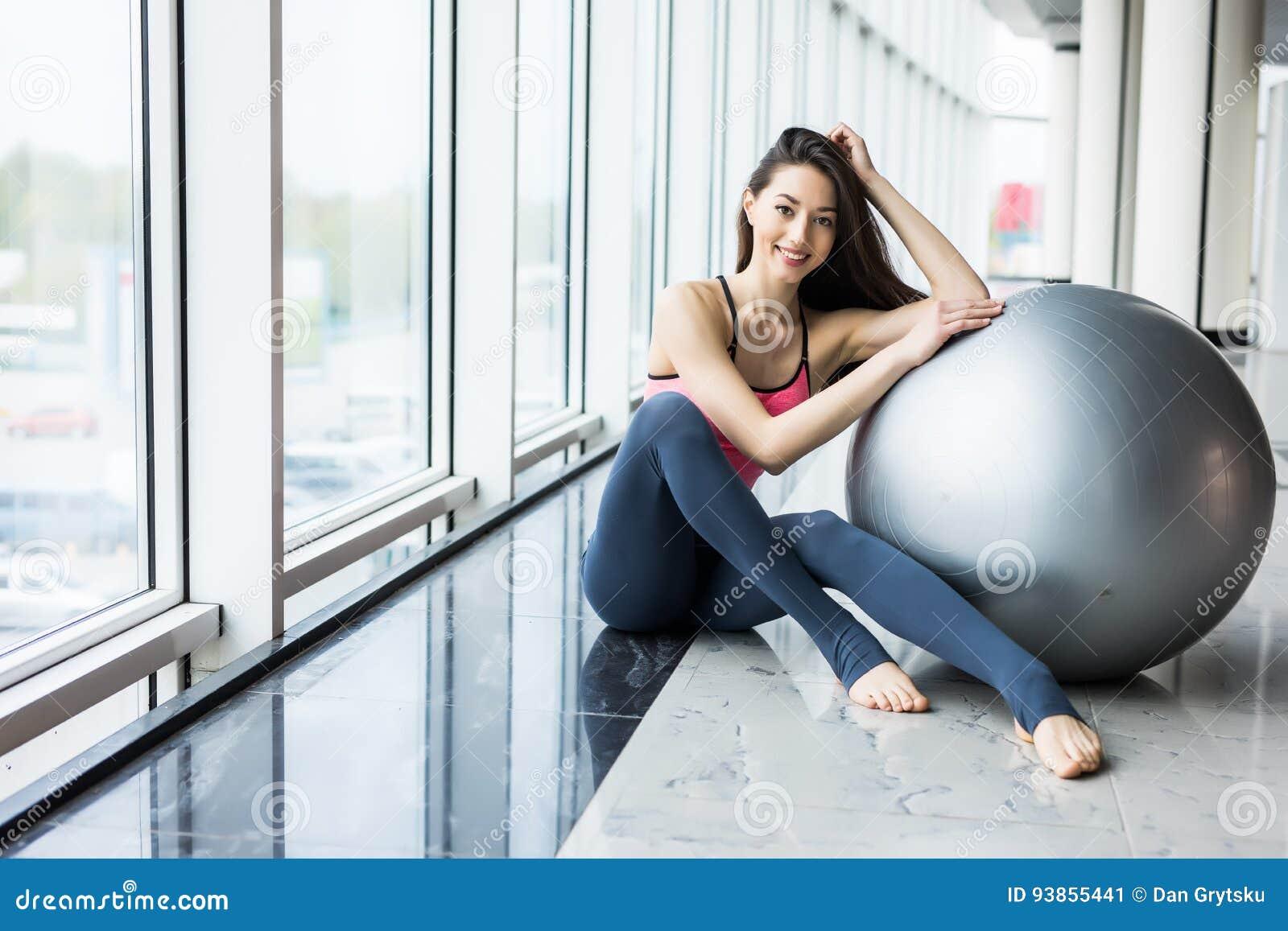 Γυναίκα που επιλύει με τη σφαίρα άσκησης στη γυμναστική Γυναίκα Pilates που κάνει τις ασκήσεις στο δωμάτιο γυμναστικής workout με