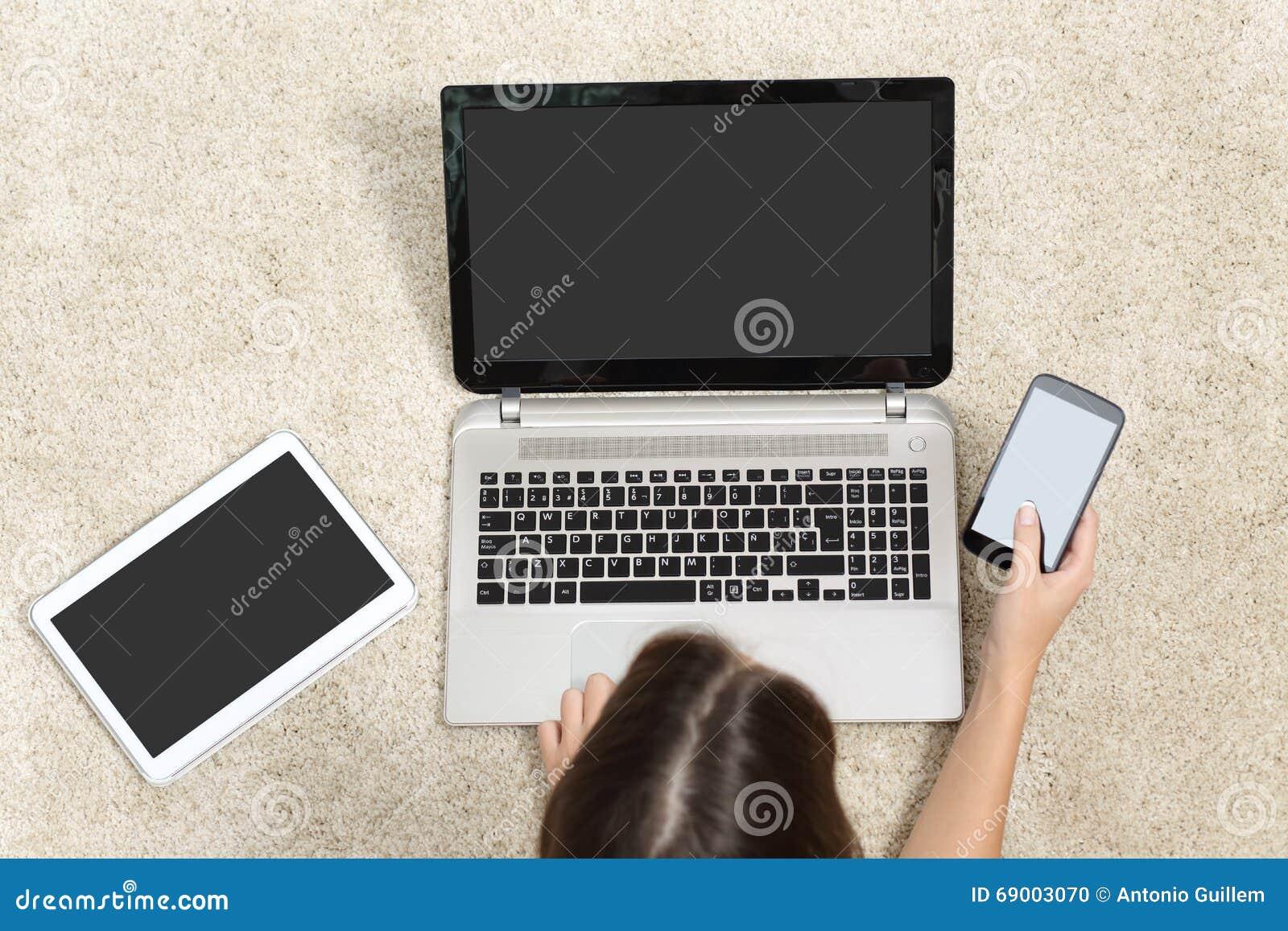 Γυναίκα που εργάζεται με τις πολλαπλάσιες οθόνες συσκευών