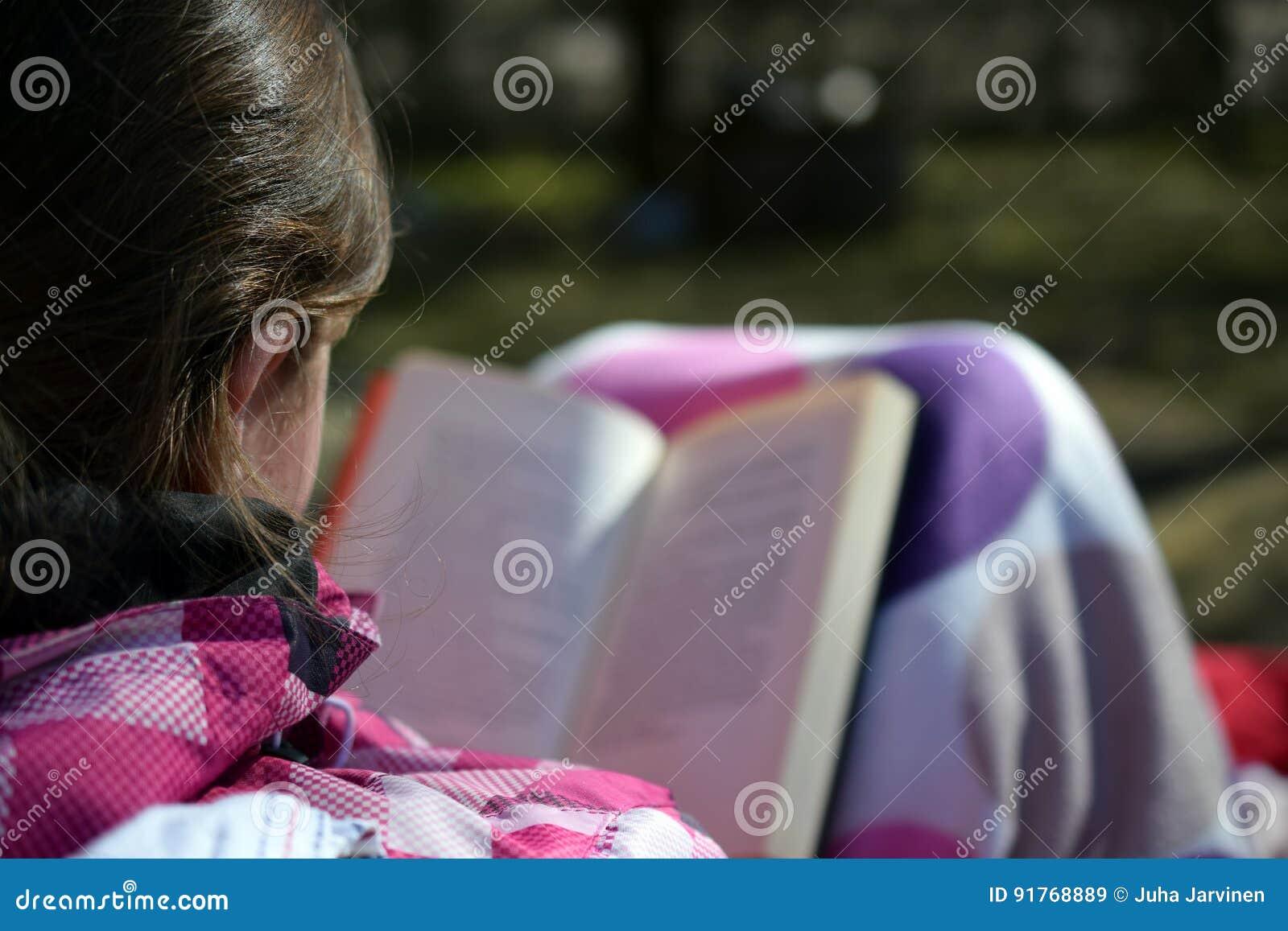Γυναίκα που διαβάζει ένα βιβλίο υπαίθριο
