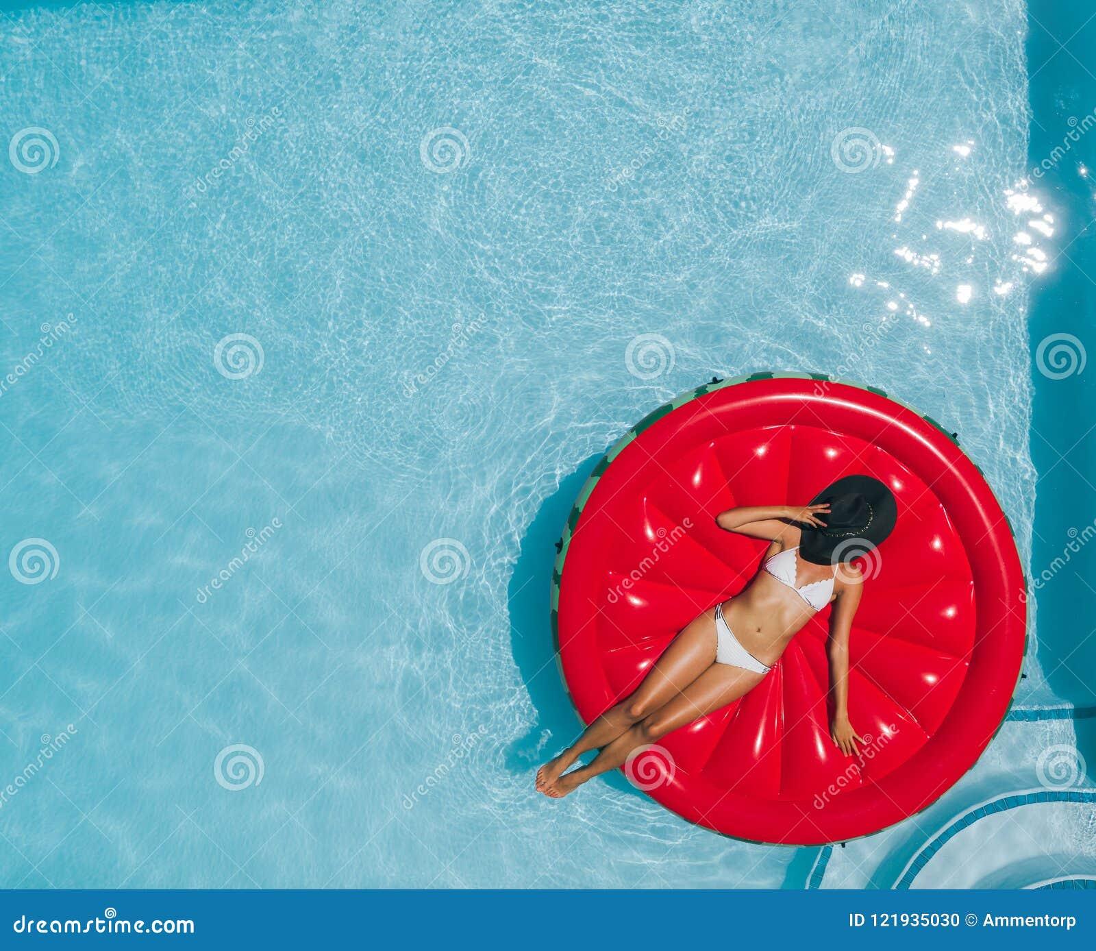 Γυναίκα που κάνει ηλιοθεραπεία στο επιπλέον στρώμα στην πισίνα