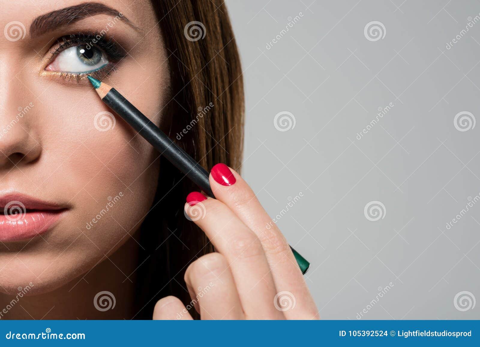 Γυναίκα που κάνει makeup με το καλλυντικό μολύβι