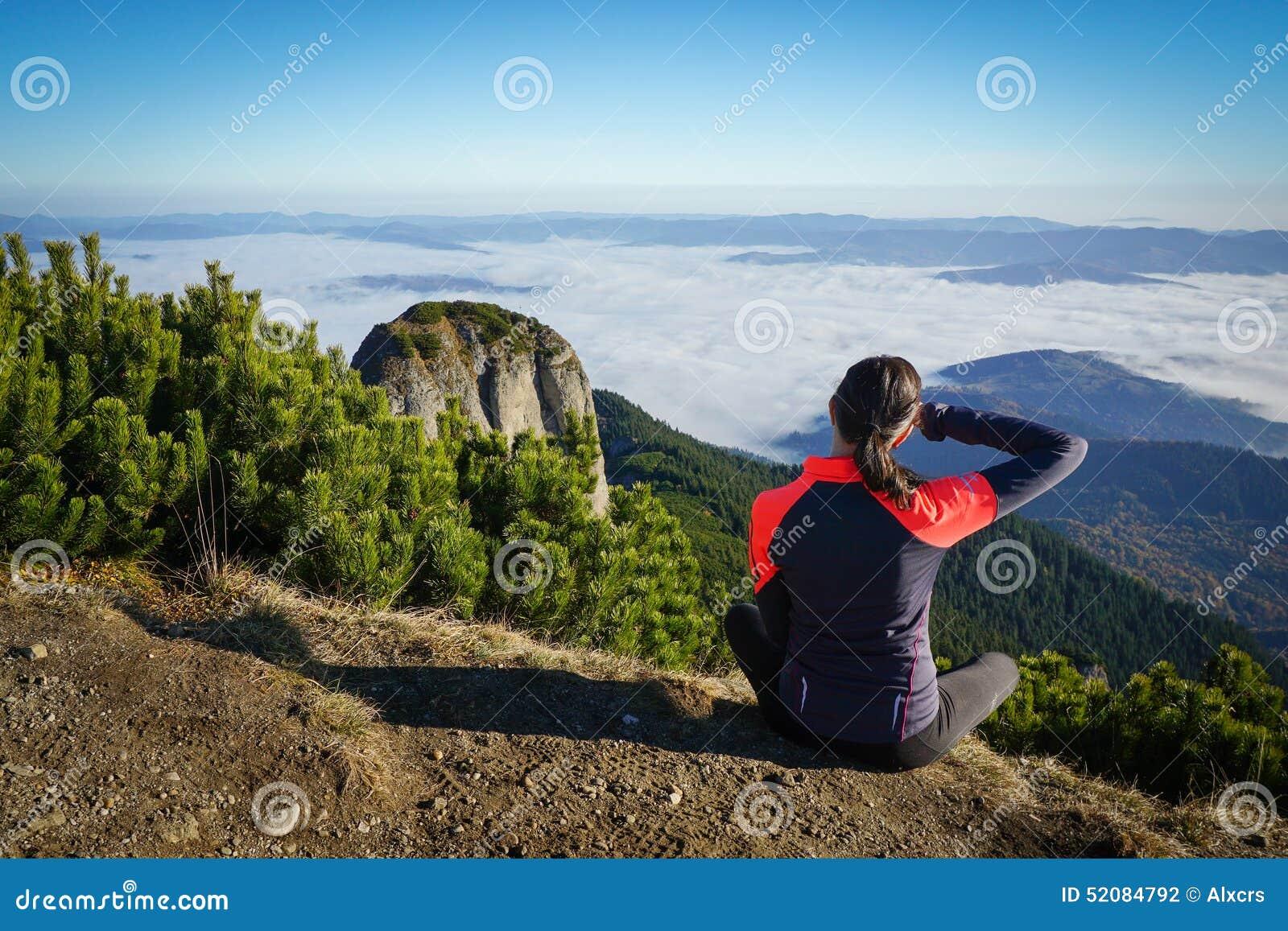 Γυναίκα που κοιτάζει στον ορίζοντα στα βουνά