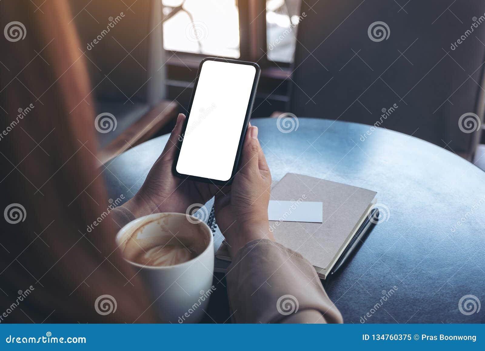 Γυναίκα που κρατά και που χρησιμοποιεί ένα μαύρο κινητό τηλέφωνο με την κενή οθόνη για την προσοχή με το φλυτζάνι σημειωματάριων