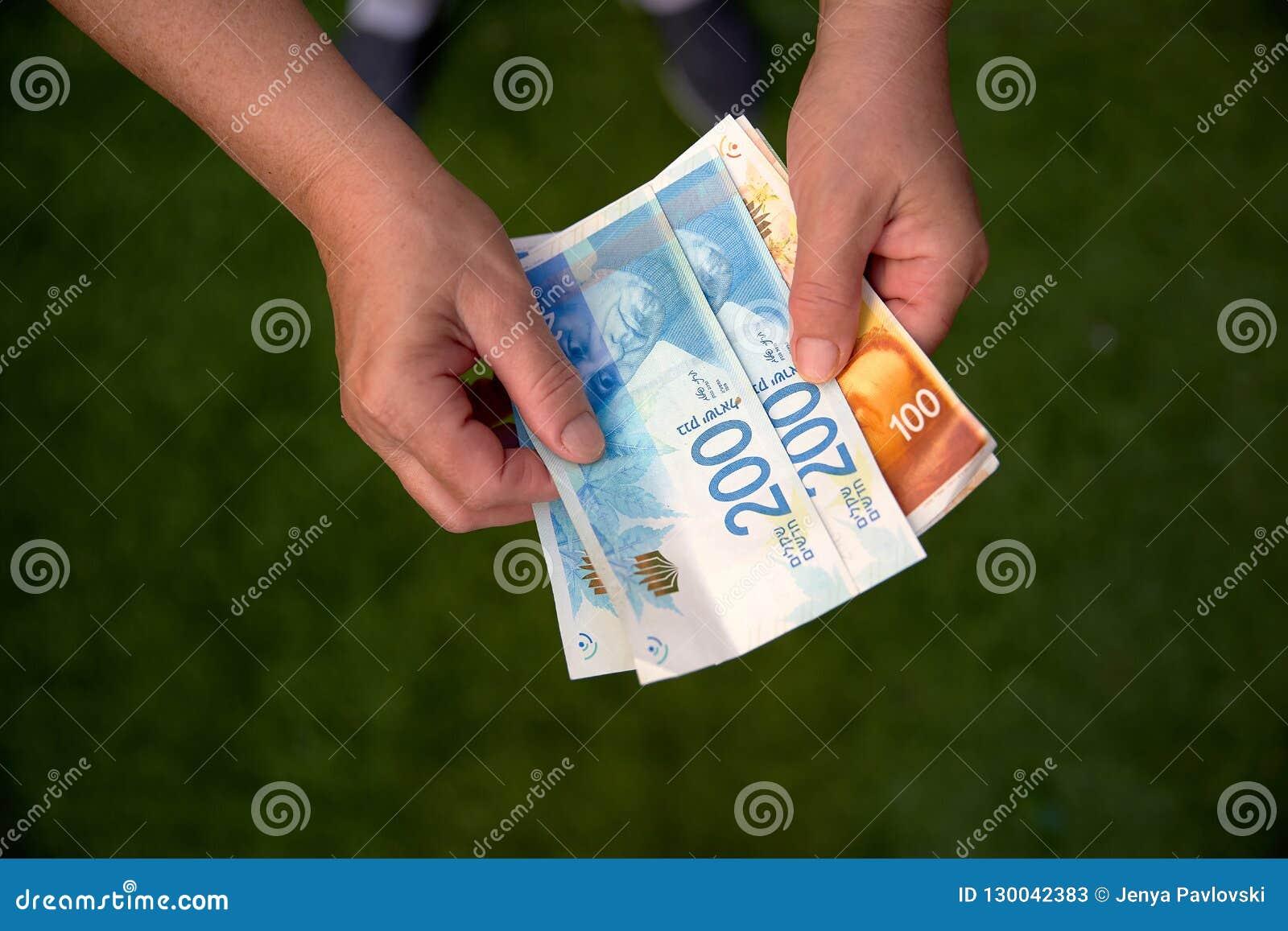 Γυναίκα που κρατά μια δέσμη των ισραηλινών νέων τραπεζογραμματίων Shekel στα χέρια της