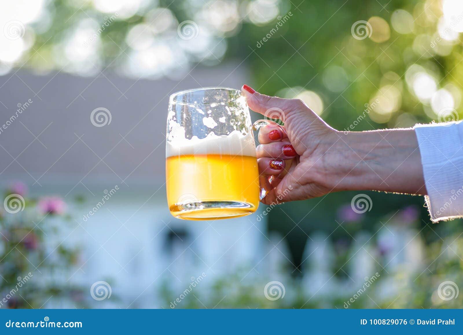 γυναίκα που κρατά μια κούπα γυαλιού της μπύρας το καλοκαίρι