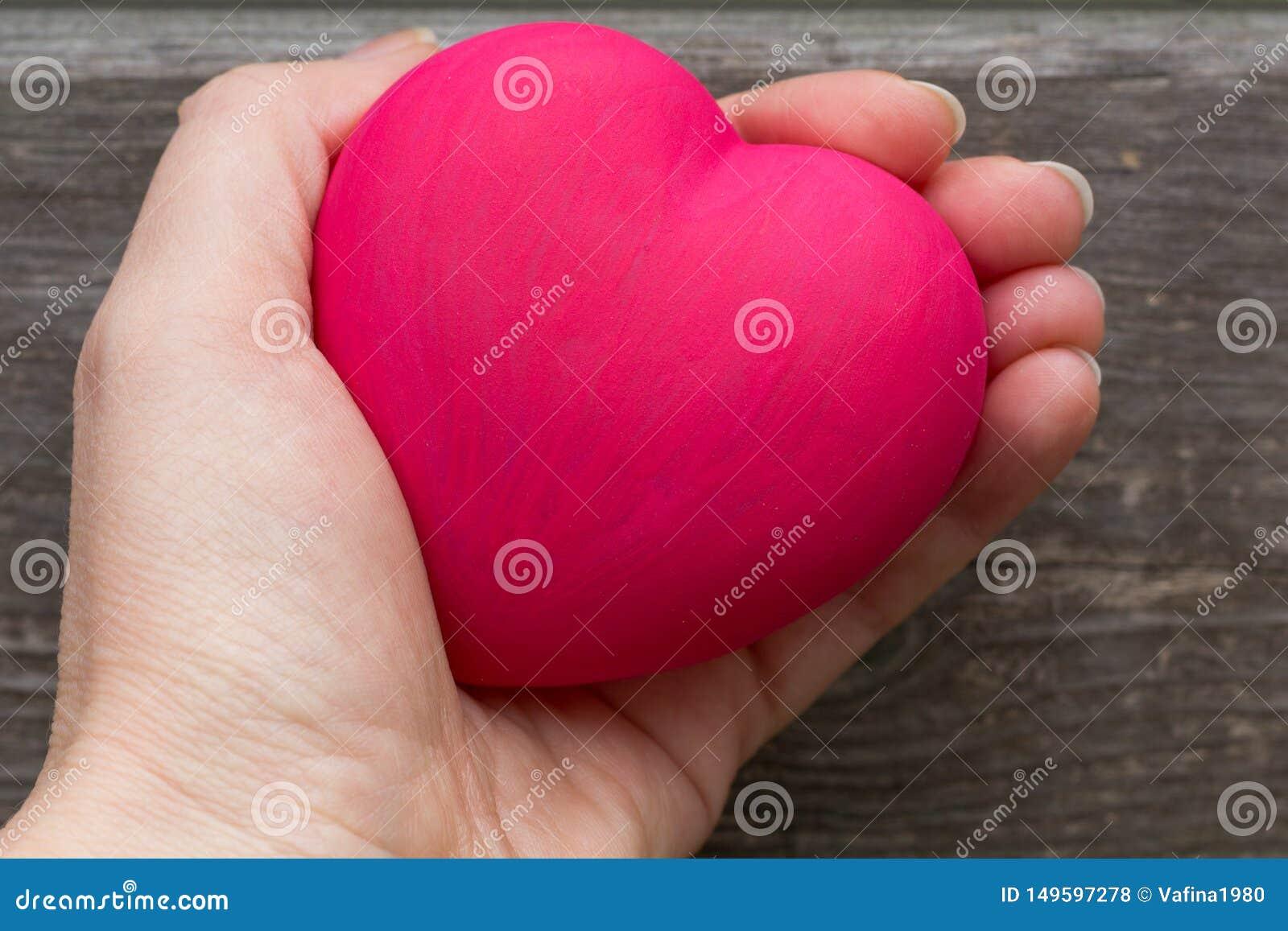 Γυναίκα που κρατά την κόκκινη καρδιά στα χέρια