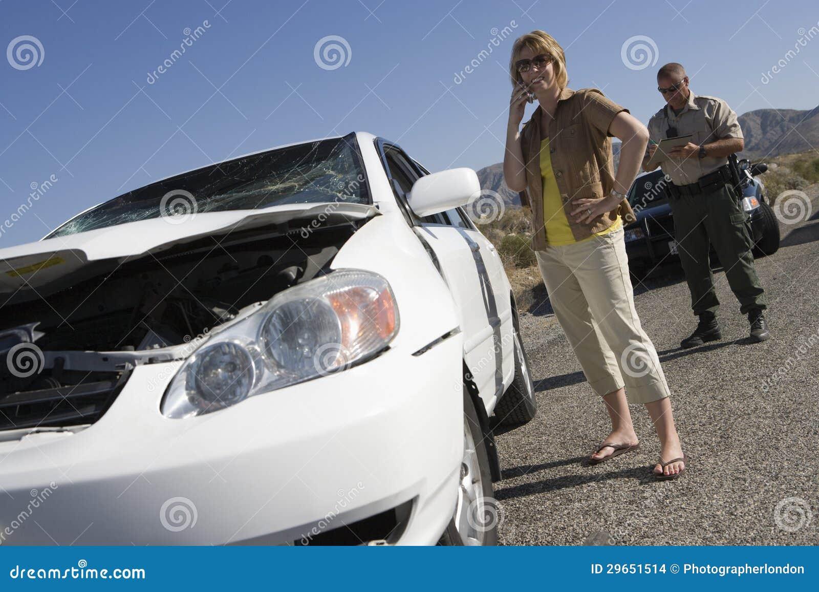 Γυναίκα που μιλά στο κινητό τηλέφωνο με το εισιτήριο γραψίματος σπολών κυκλοφορίας στην οδό
