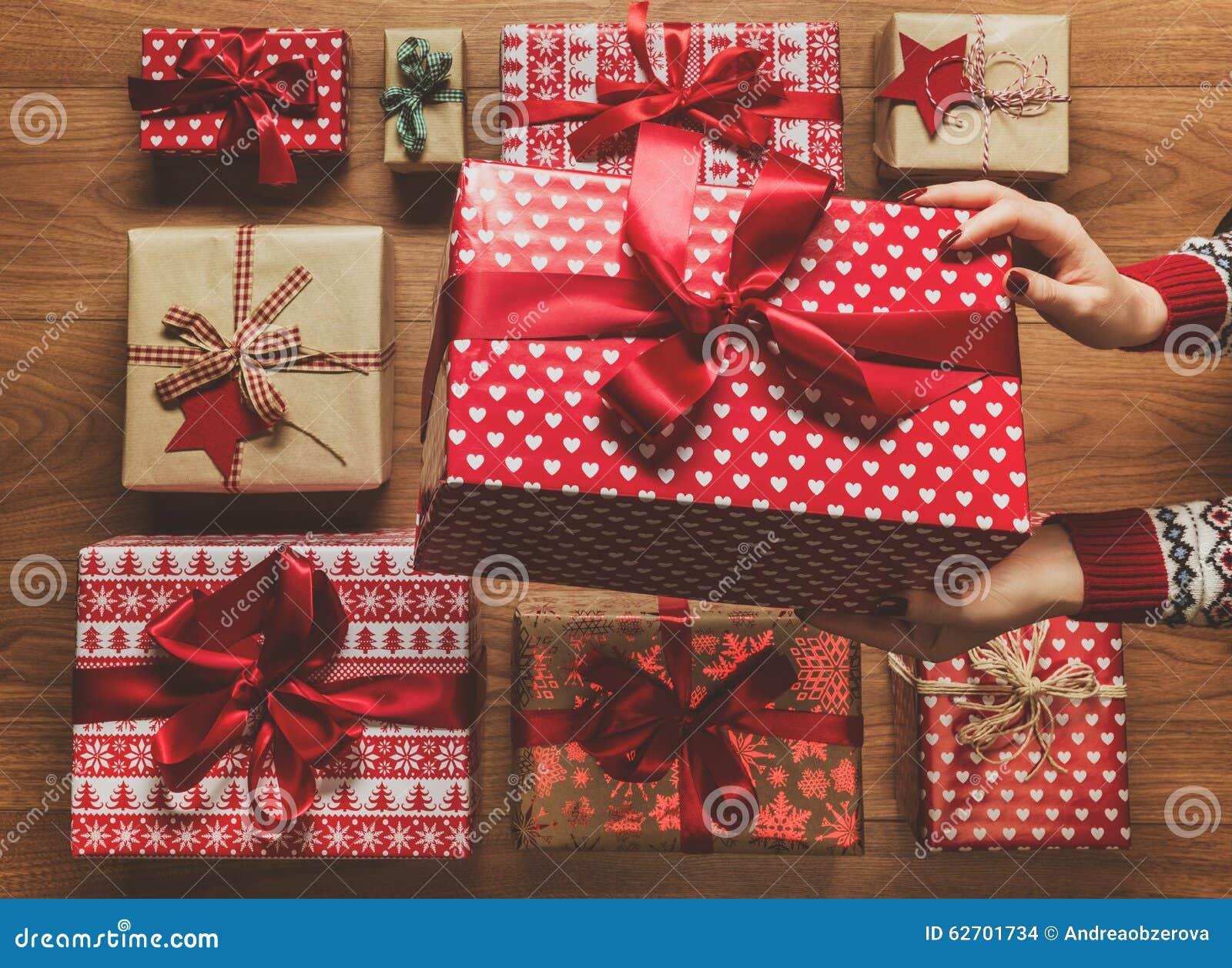 Γυναίκα που οργανώνει τα υπέροχα τυλιγμένα εκλεκτής ποιότητας χριστουγεννιάτικα δώρα, εικόνα με την ελαφριά ομίχλη, άποψη άνωθεν