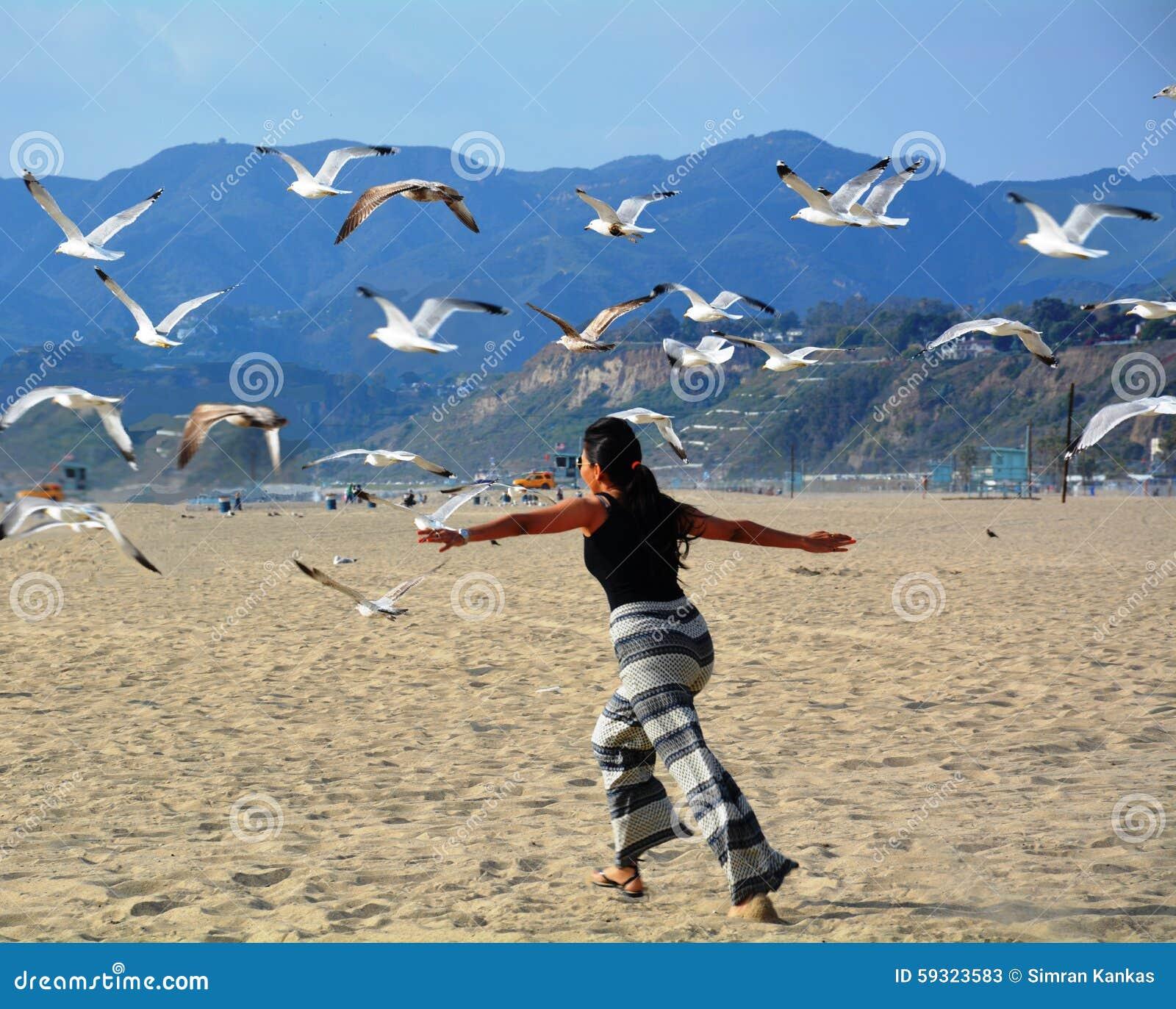 Γυναίκα που πετά με τα πουλιά θάλασσας στην παραλία