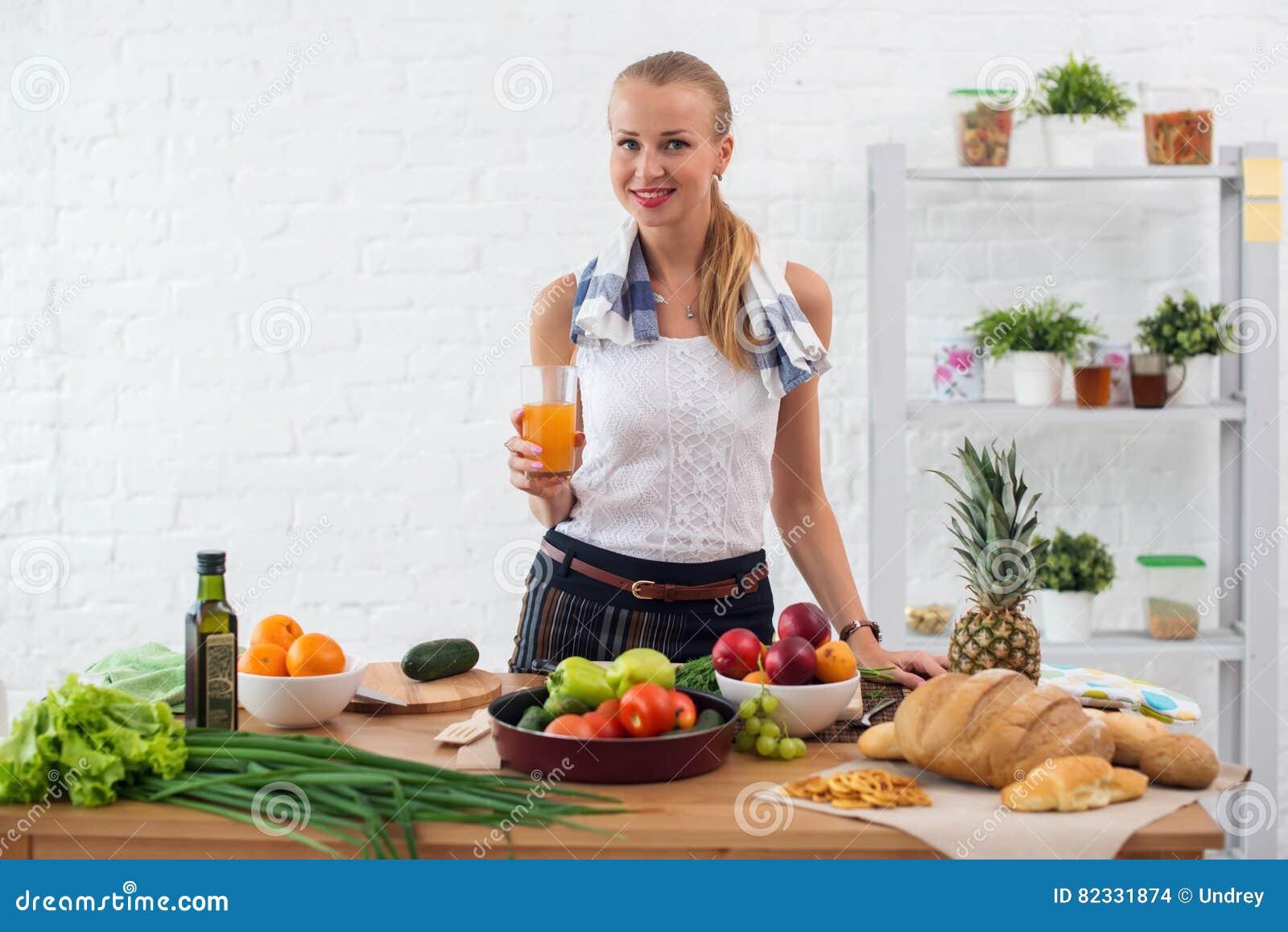 Γυναίκα που προετοιμάζει το γεύμα σε μια κουζίνα, πίνοντας το μαγείρεμα έννοιας χυμού, μαγειρικός, υγιής τρόπος ζωής
