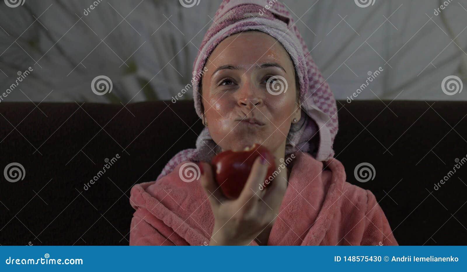 Γυναίκα που προσέχει έναν πρόσφατο - κινηματογράφος νύχτας στη TV, που τρώει ένα μήλο Μπουρνούζι, του προσώπου μάσκα