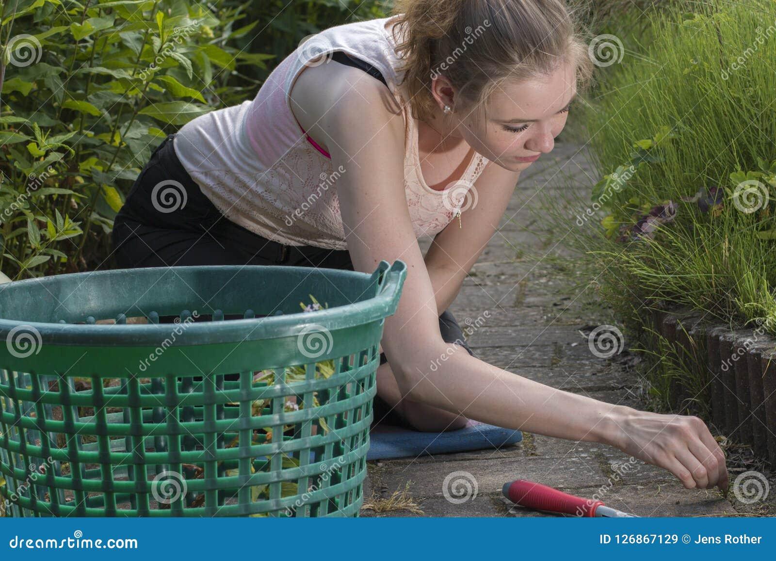 Γυναίκα που τραβά τα ζιζάνια στον κήπο