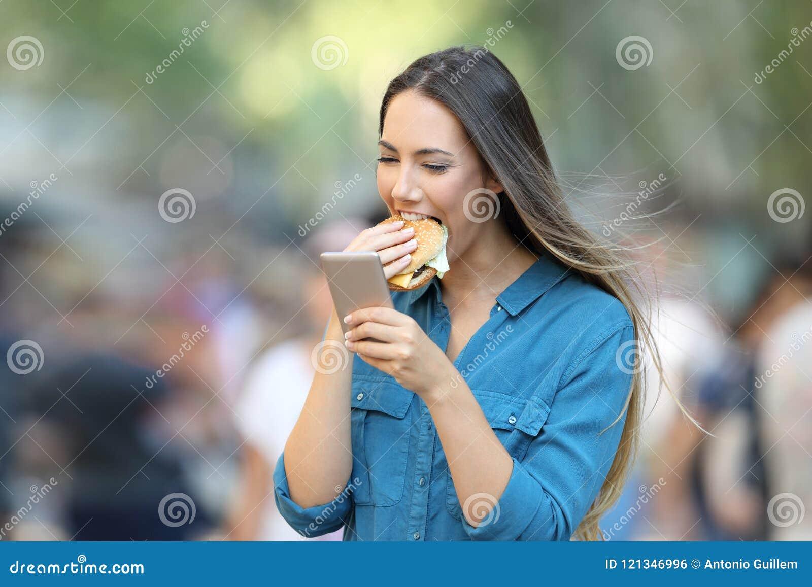 Γυναίκα που τρώει burger που κρατά ένα έξυπνο τηλέφωνο