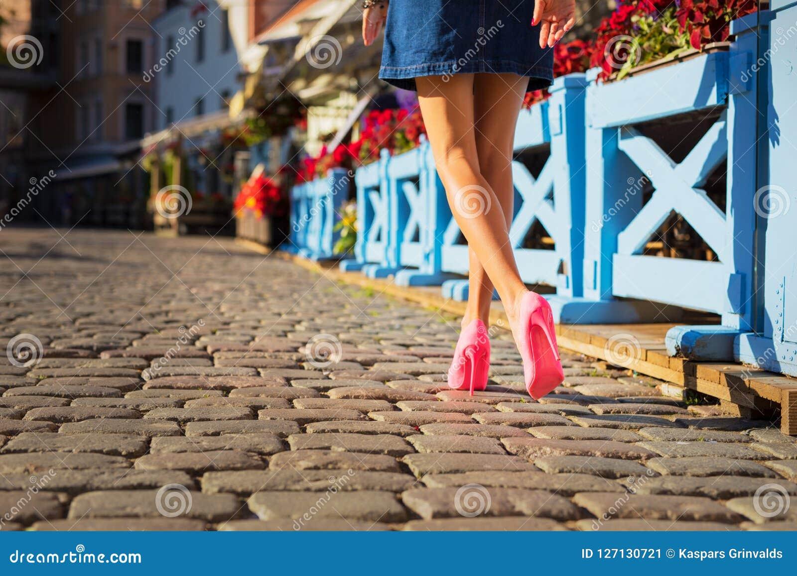 Γυναίκα που φορά τα εκφραστικά ρόδινα παπούτσια