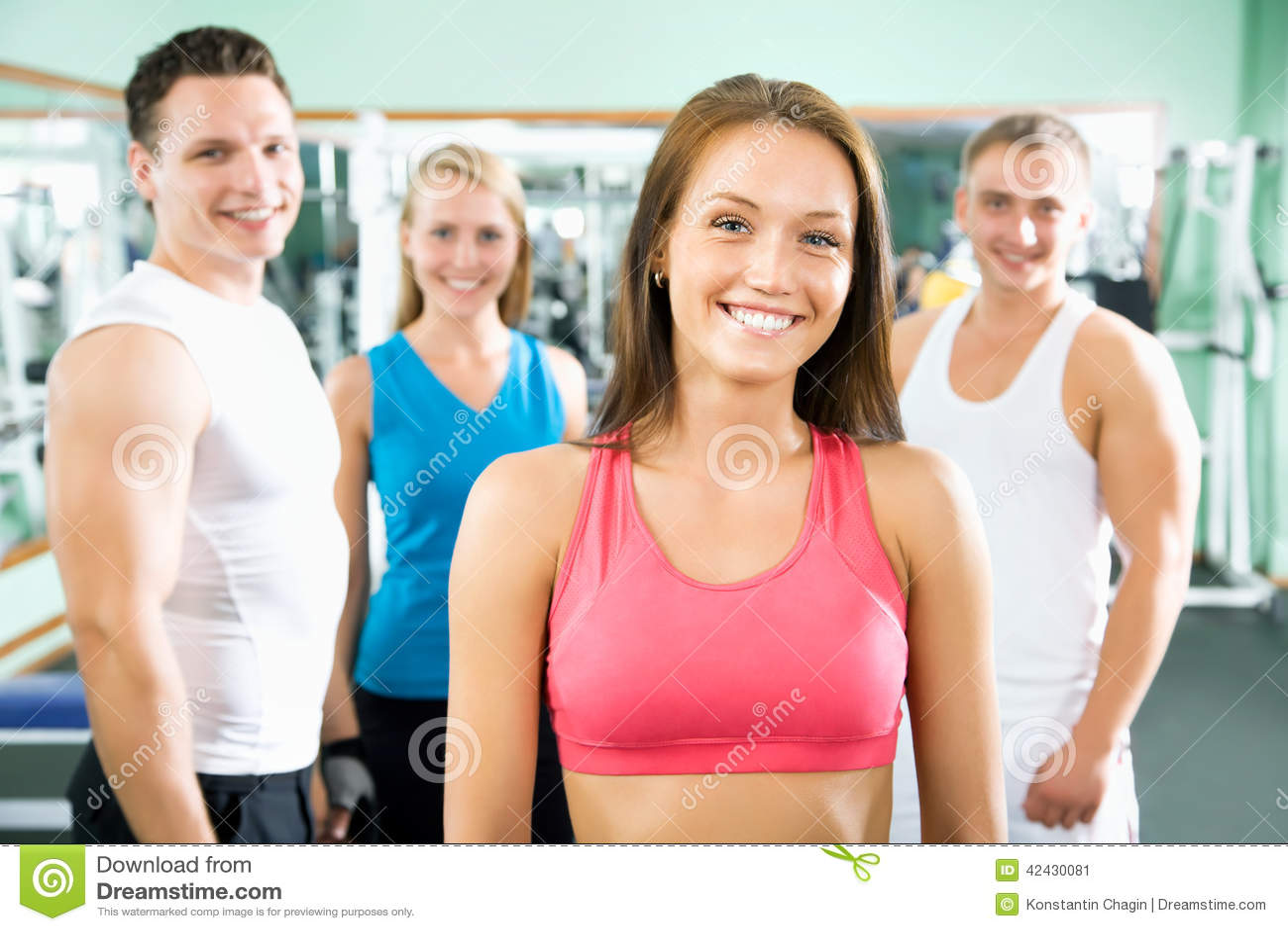 Γυναίκα που χαμογελά μπροστά από μια ομάδα ανθρώπων γυμναστικής