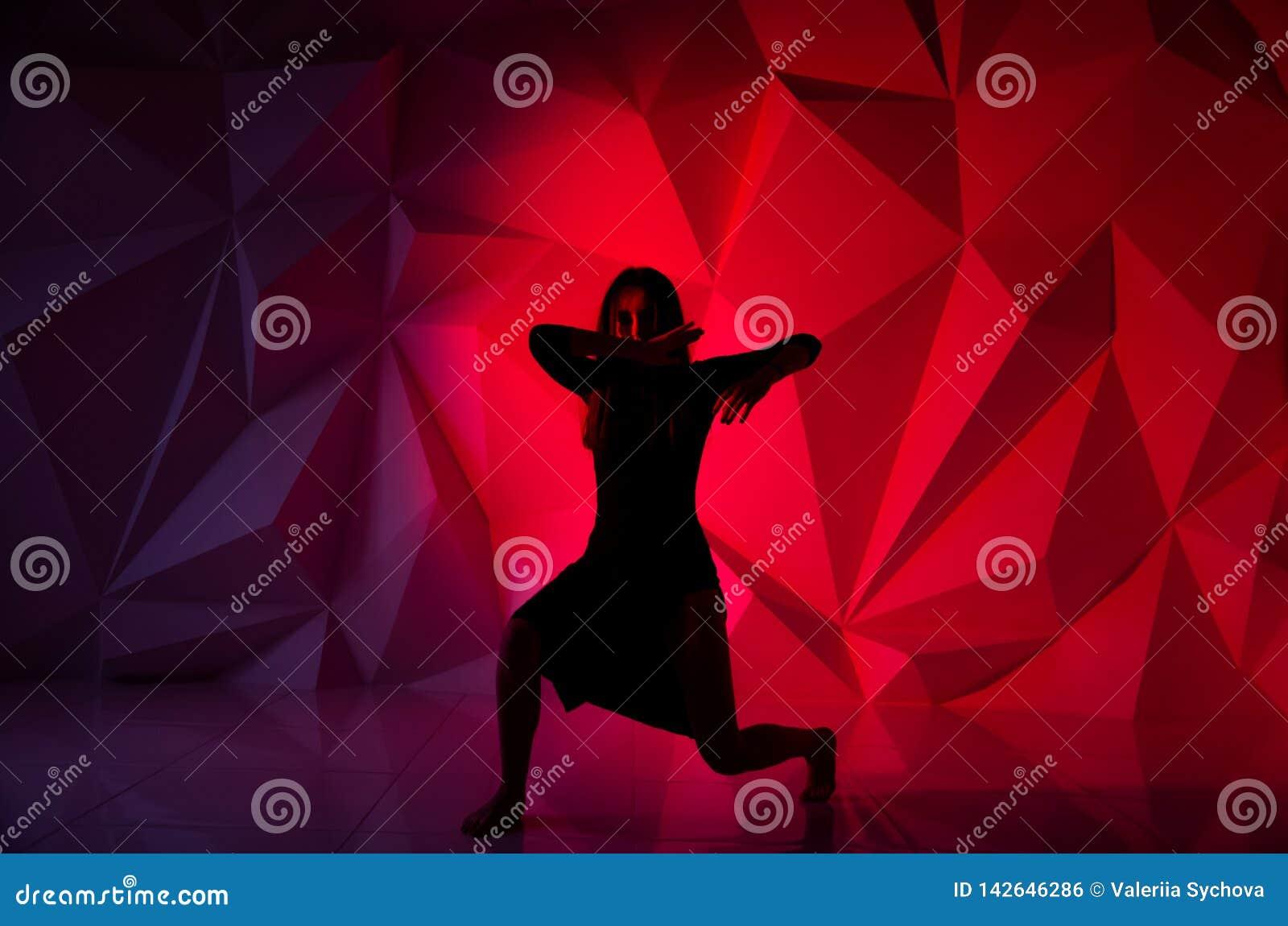 Γυναίκα που χορεύει στο υπόβαθρο ενός όμορφου πολύχρωμου τοίχου Προκλητικό λεπτό μόνο κορίτσι με τη μακριά μαύρη τρίχα στο α