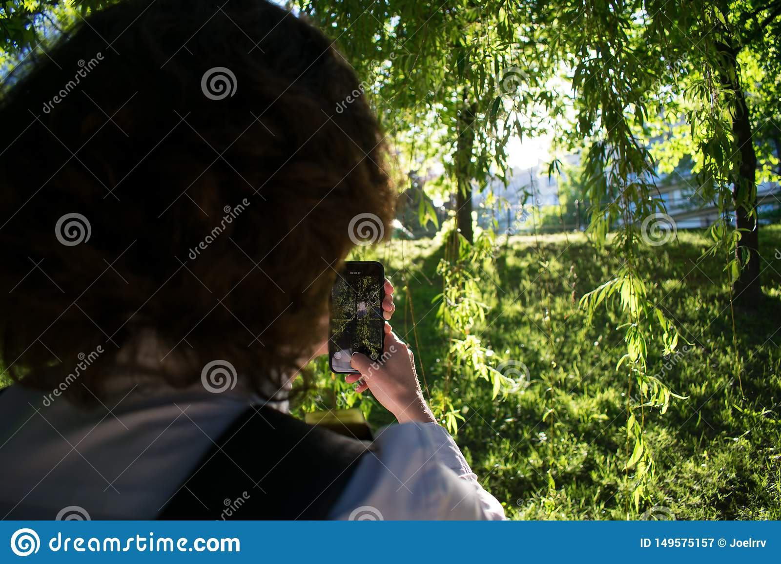 Γυναίκα που χρησιμοποιεί το smartphone για να συλλάβει το όμορφο ηλιοβασίλεμα στο πάρκο
