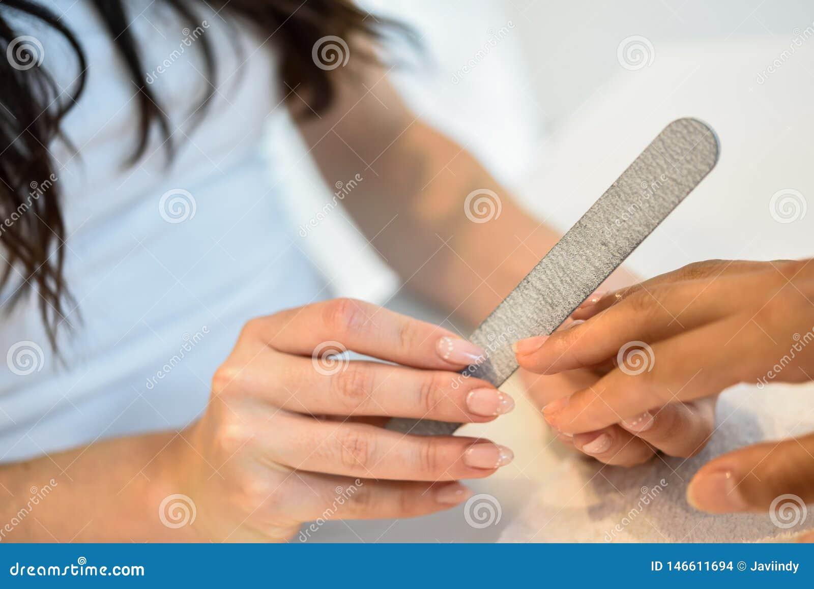 Γυναίκα σε ένα σαλόνι καρφιών που λαμβάνει ένα μανικιούρ με το αρχείο καρφιών