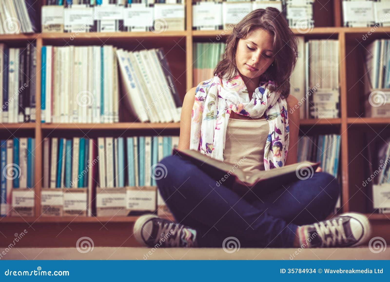 Γυναίκα σπουδαστής ενάντια στο ράφι που διαβάζει ένα βιβλίο στο πάτωμα βιβλιοθηκών