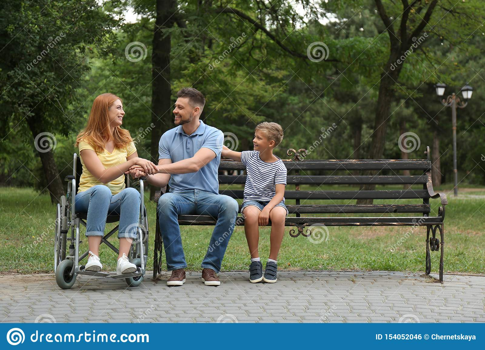 Γυναίκα στην αναπηρική καρέκλα με την οικογένειά της