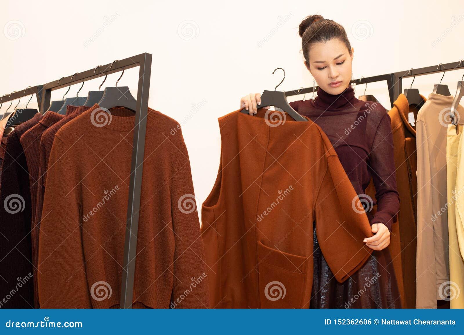 Γυναίκα στην επίλεκτη νέα συλλογή φορεμάτων στο ράφι