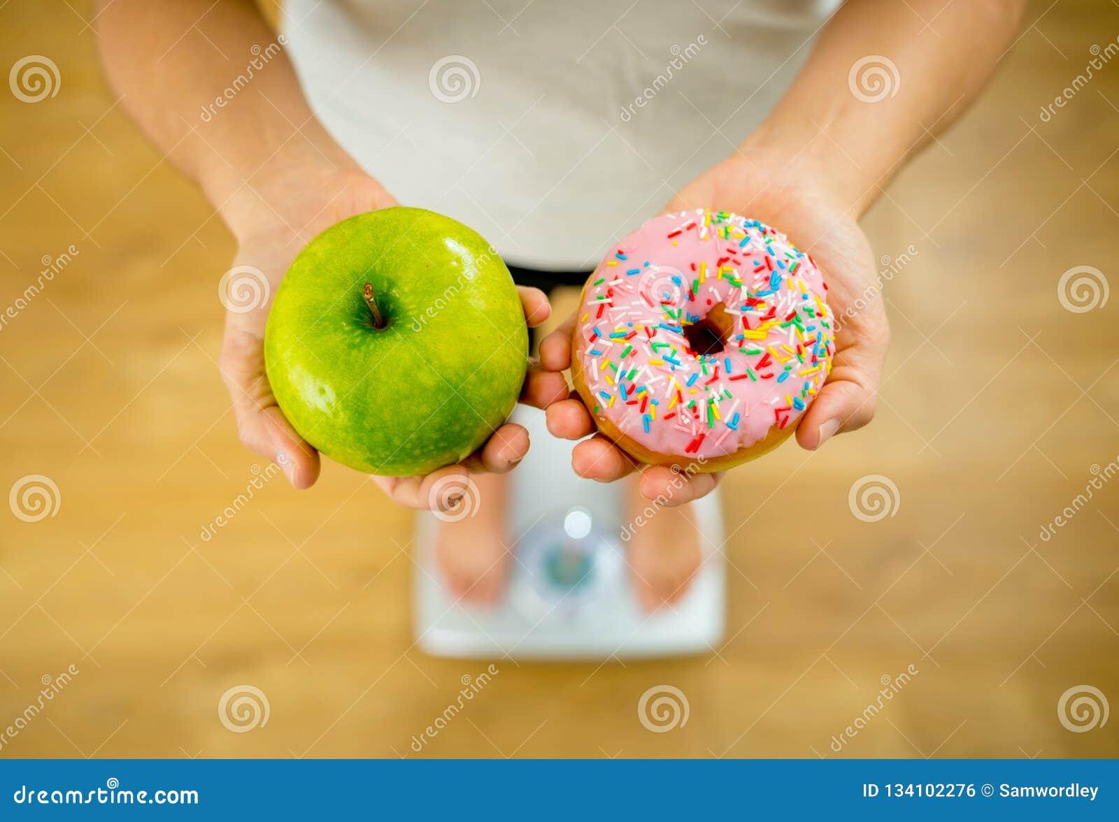 Γυναίκα στην κλίμακα που μετρά το μήλο εκμετάλλευσης βάρους και donuts που επιλέγει μεταξύ των υγιών ή ανθυγειινών τροφίμων