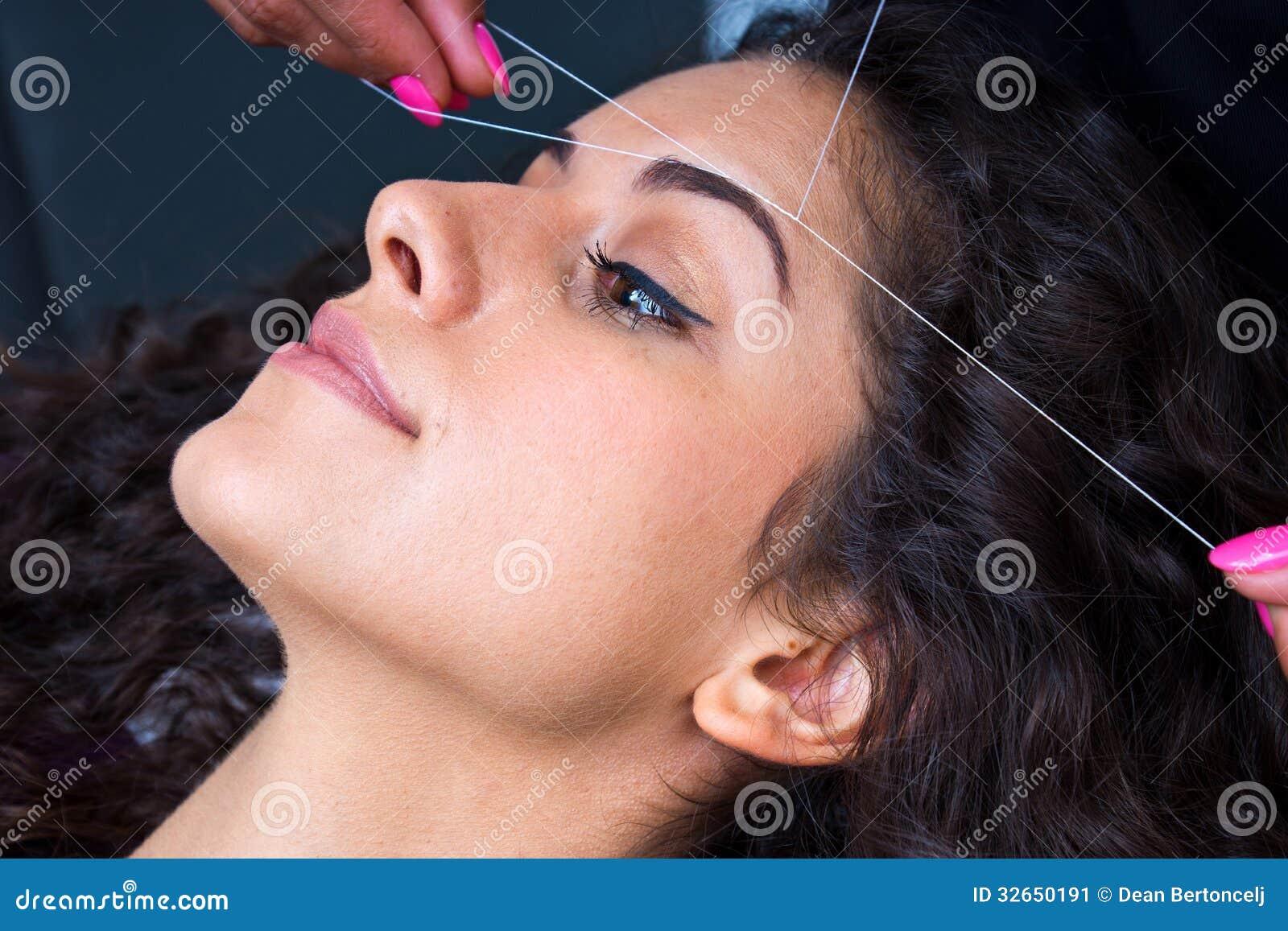 Γυναίκα στην του προσώπου αφαίρεση τρίχας που περνά κλωστή στη διαδικασία