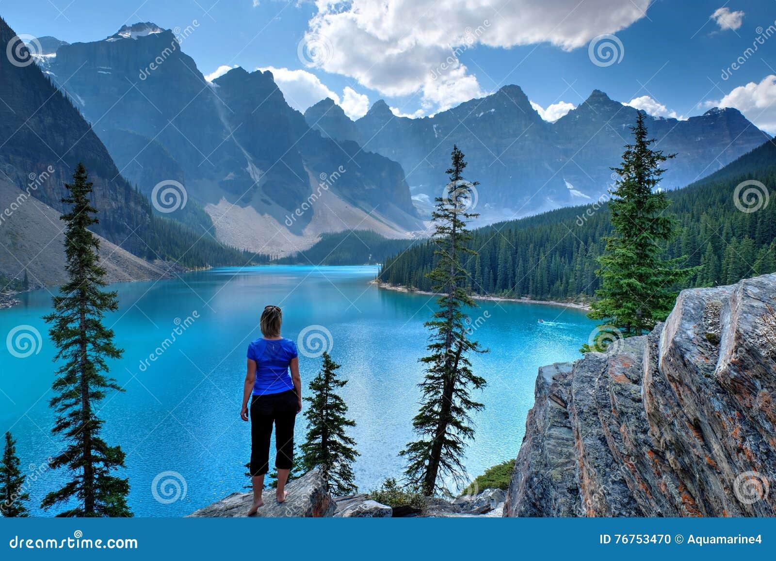 Γυναίκα στον απότομο βράχο στη φυσικά λίμνη και τα βουνά