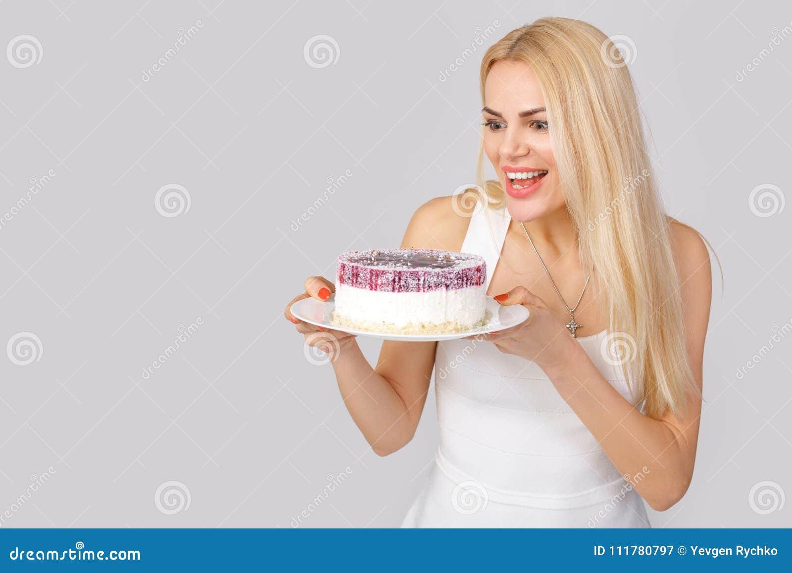 Γυναίκα στο άσπρο κέικ εκμετάλλευσης φορεμάτων