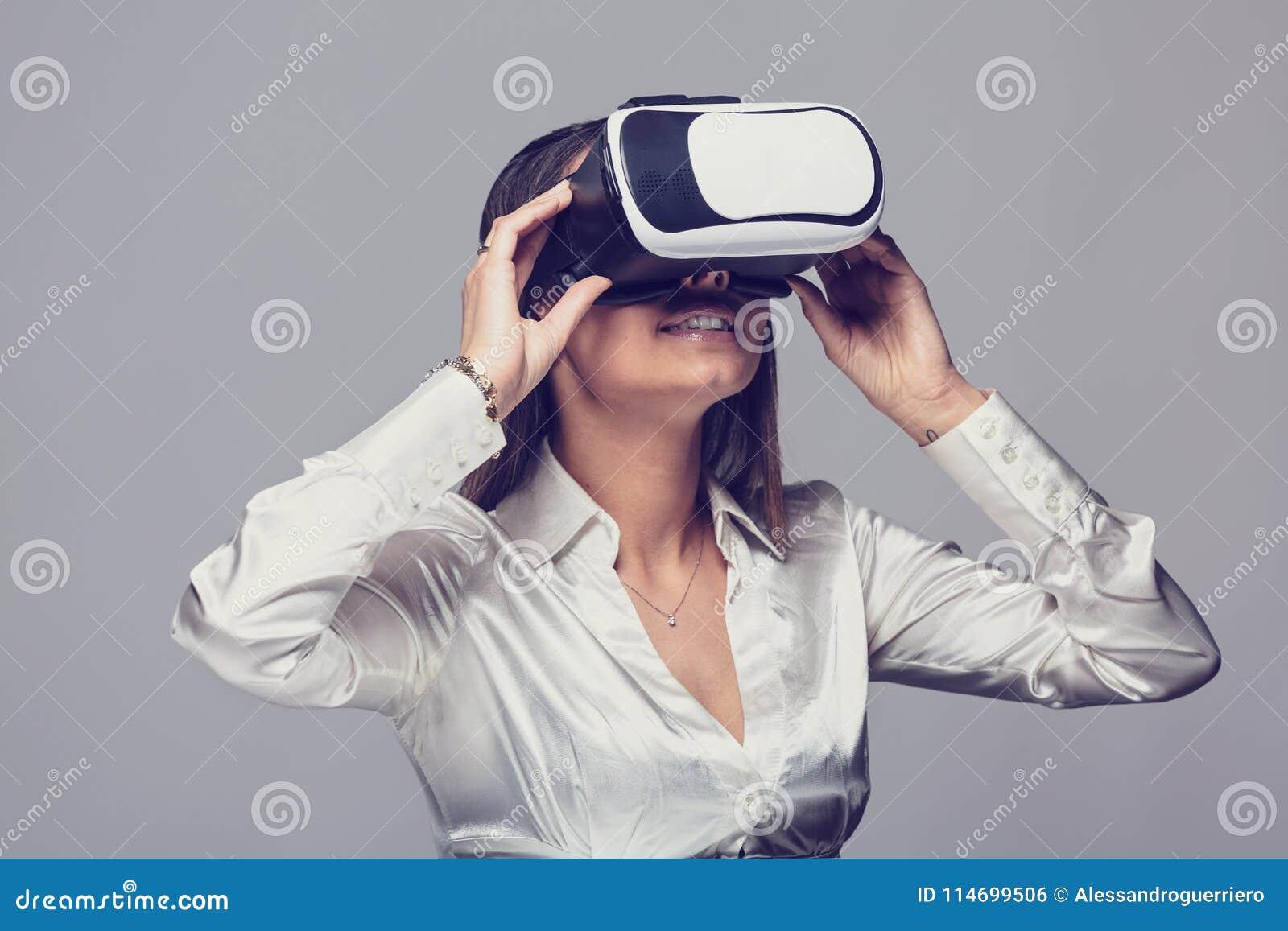 Γυναίκα στο άσπρο πουκάμισο που χρησιμοποιεί vr τα γυαλιά