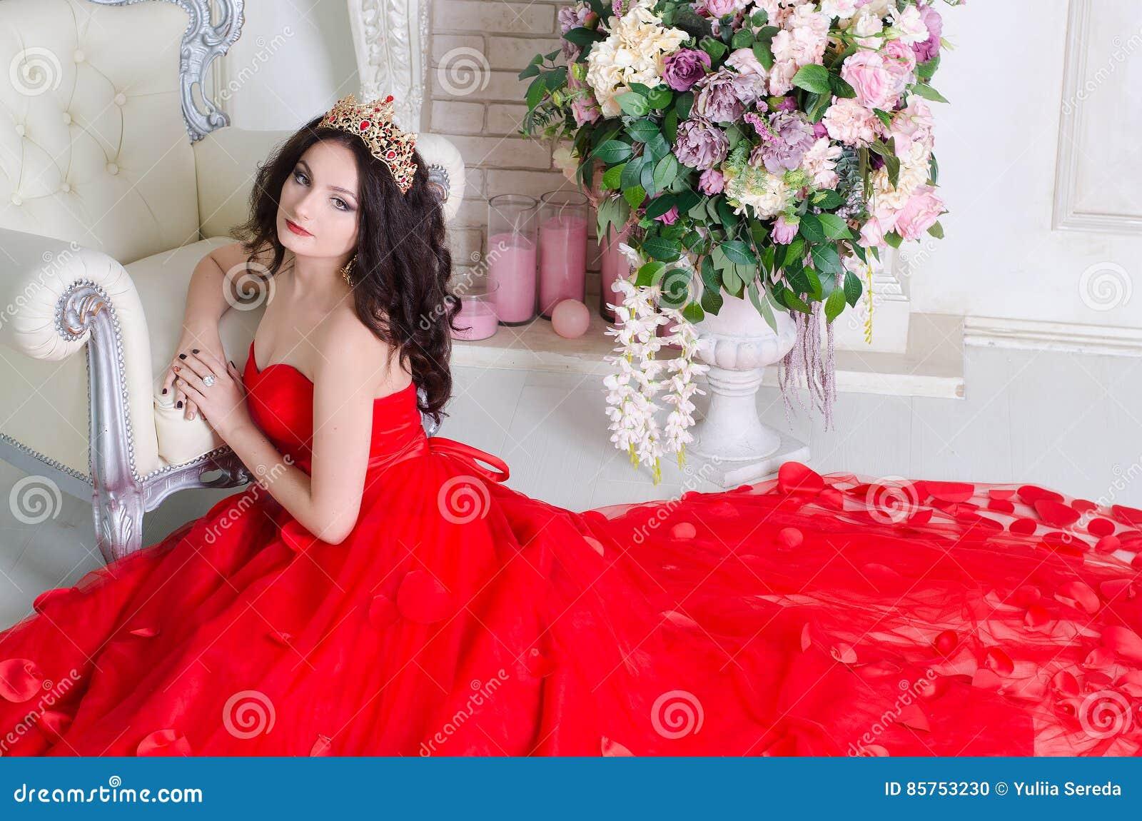0193604f018e Όμορφη γυναίκα στο κόκκινο μακρύ φόρεμα με μια χρυσή κορώνα και τα  σκουλαρίκια που θέτουν τη συνεδρίαση στο πάτωμα κοντά στην καρέκλα