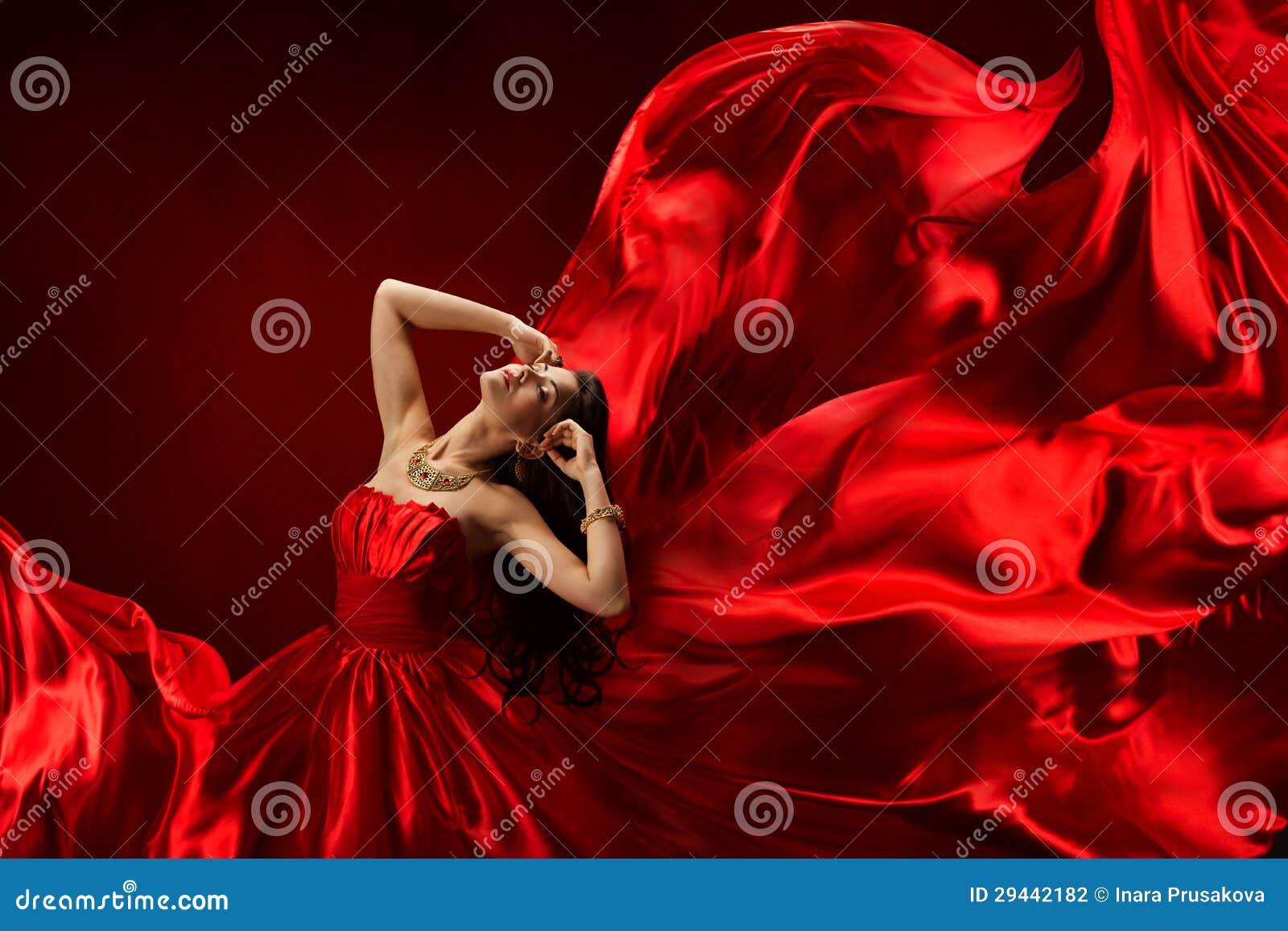Γυναίκα στο κόκκινο φόρεμα που φυσά με το πετώντας ύφασμα